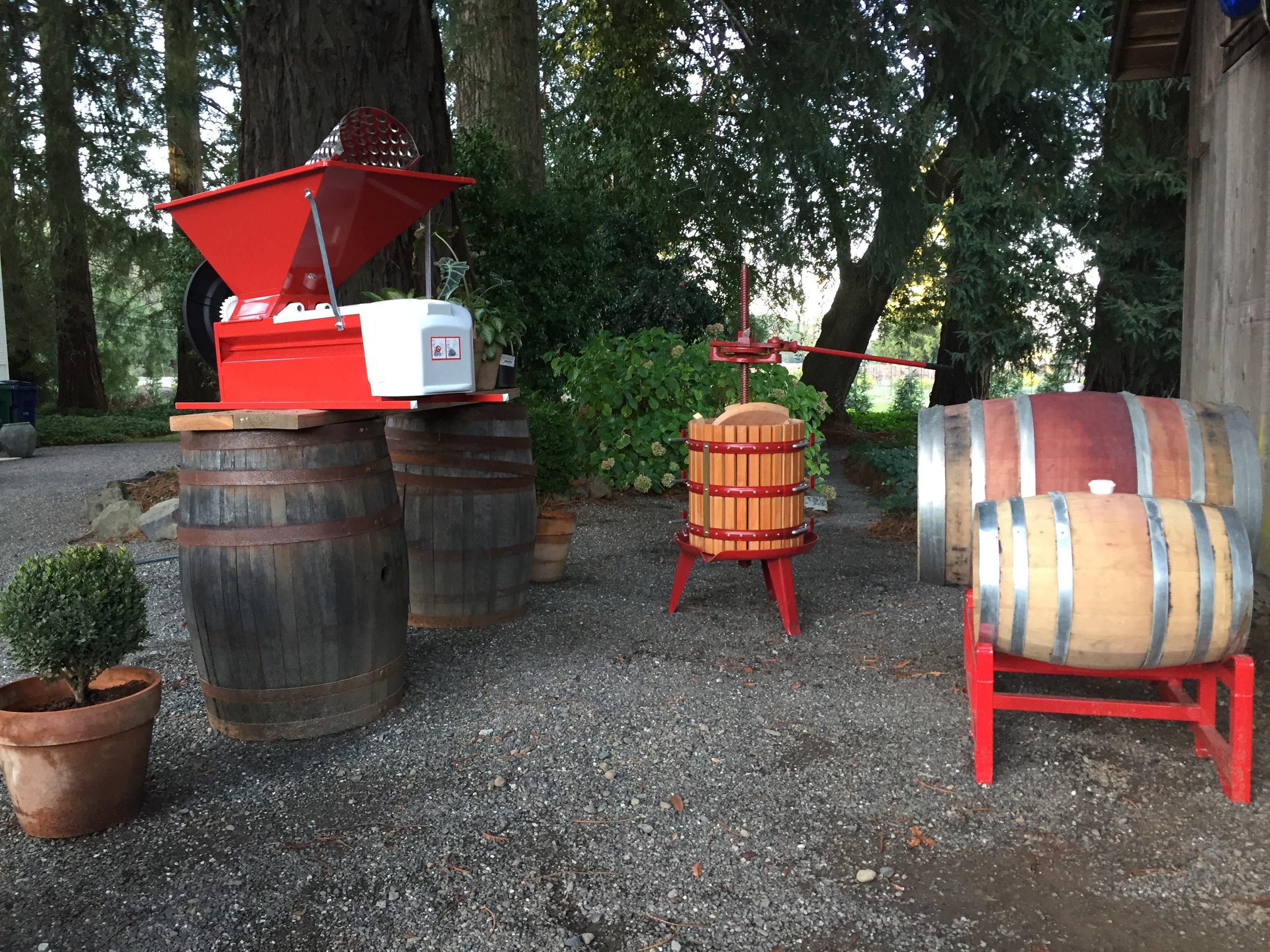 Small batch production: a hand crank crusher /destemmer, grape press, and oak barrels