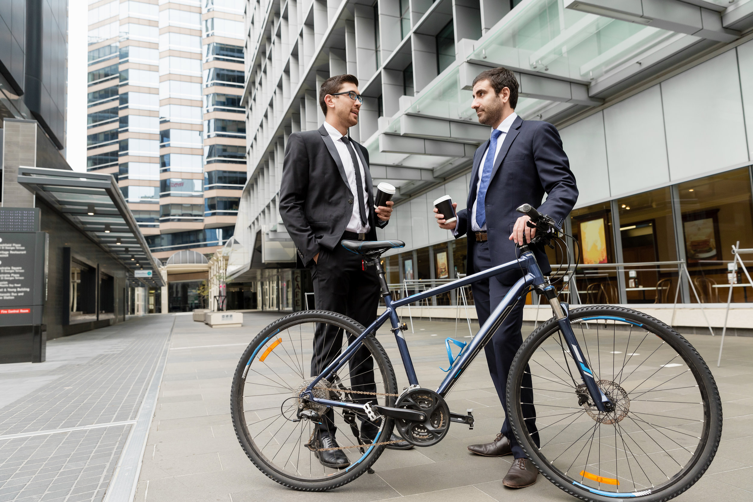 two-young-businessmen-with-a-bike-in-city-centre-P35X39T.jpg