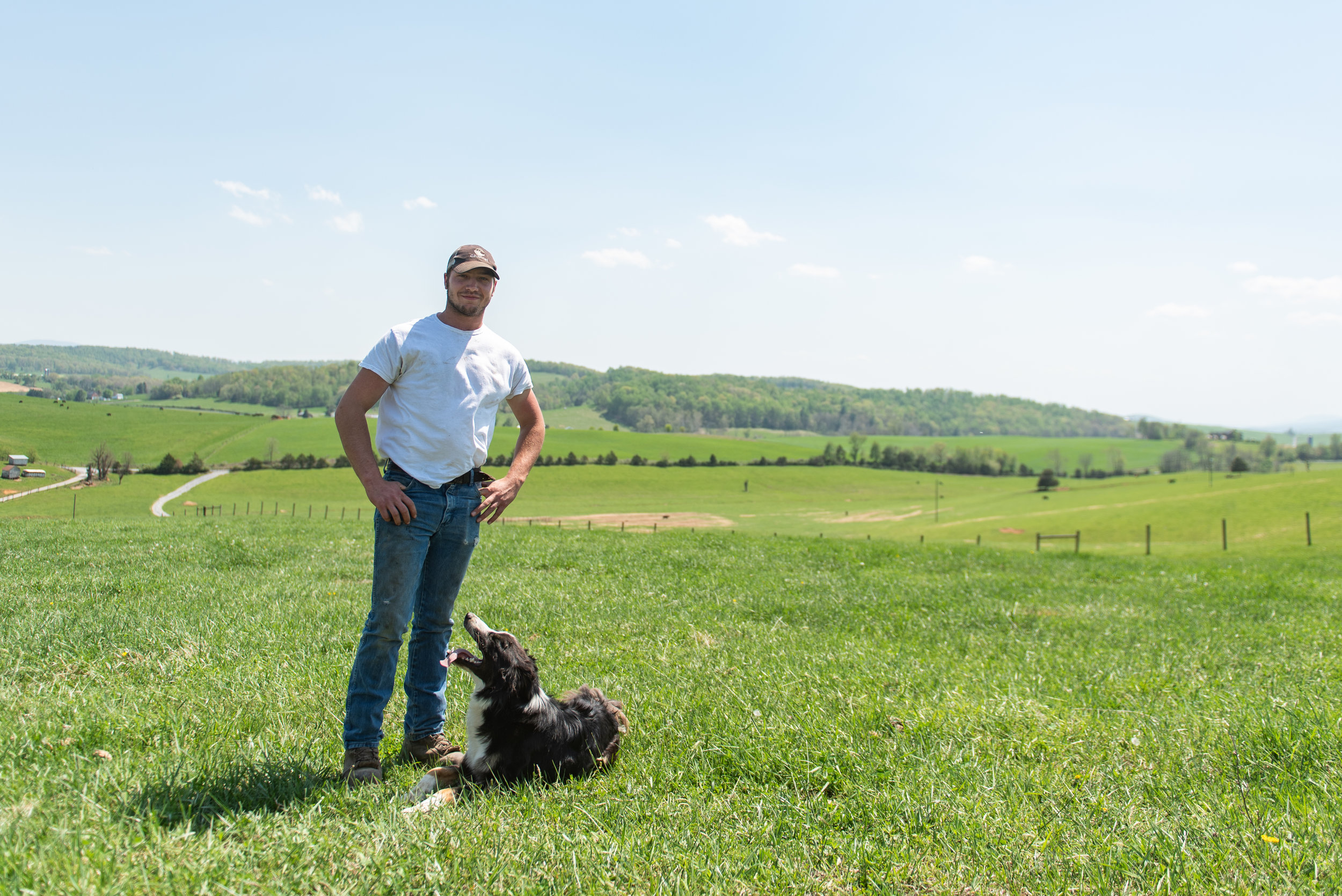 Luke Grant stands on his parent's farm with his dog, Cinch.