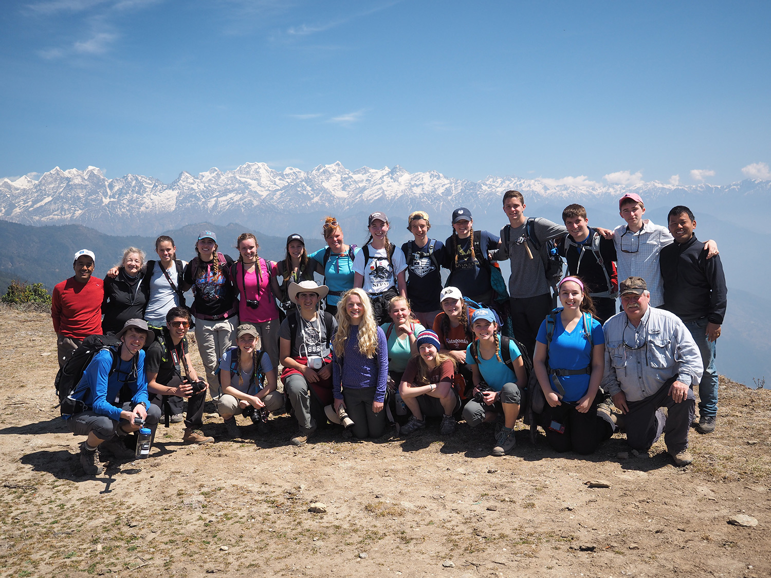 TVolunteer teacher Barb Figg (left, back row) and her husband Jim Figg (right, front row) pose with other volunteers with some of the world's highest peaks in the background.