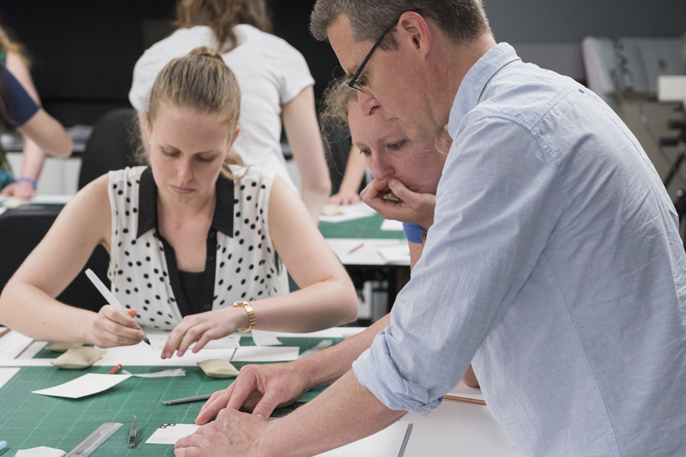 Paper conservator Peter Mitchelson demonstrates how to mount postcard with Elizabeth Gralton and Kate Ritchie
