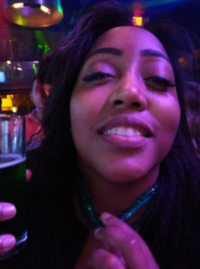 Photo Description: This is a photo of my face since you maybe wondering what I look like. With a warm and boozy expression, I'm wearing a green necklace that my mom gave me, that matches the green beer I am holding.
