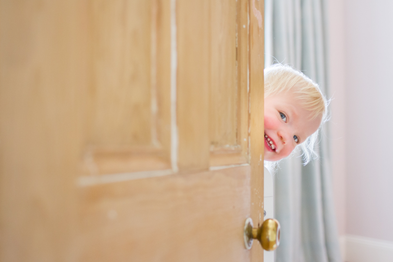 little girl poking hear around doorway