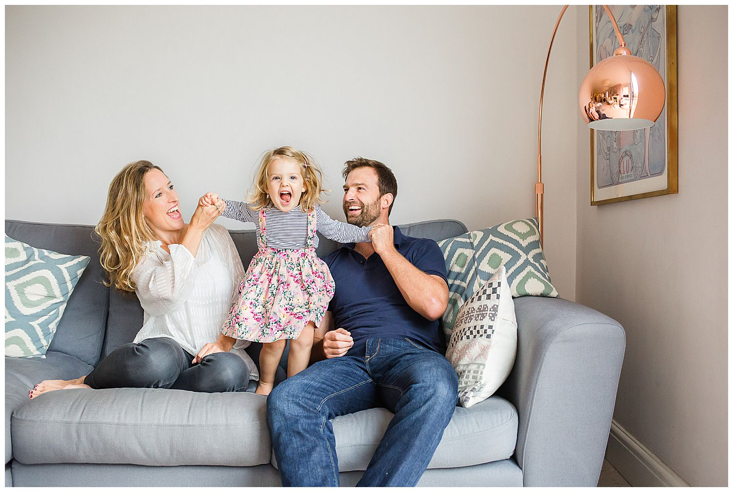 child jumping on sofa holding mum & dad's hands