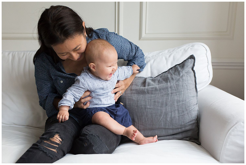 baby on mum's lap laughing
