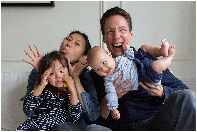 family sitting o sofa doing funny faces
