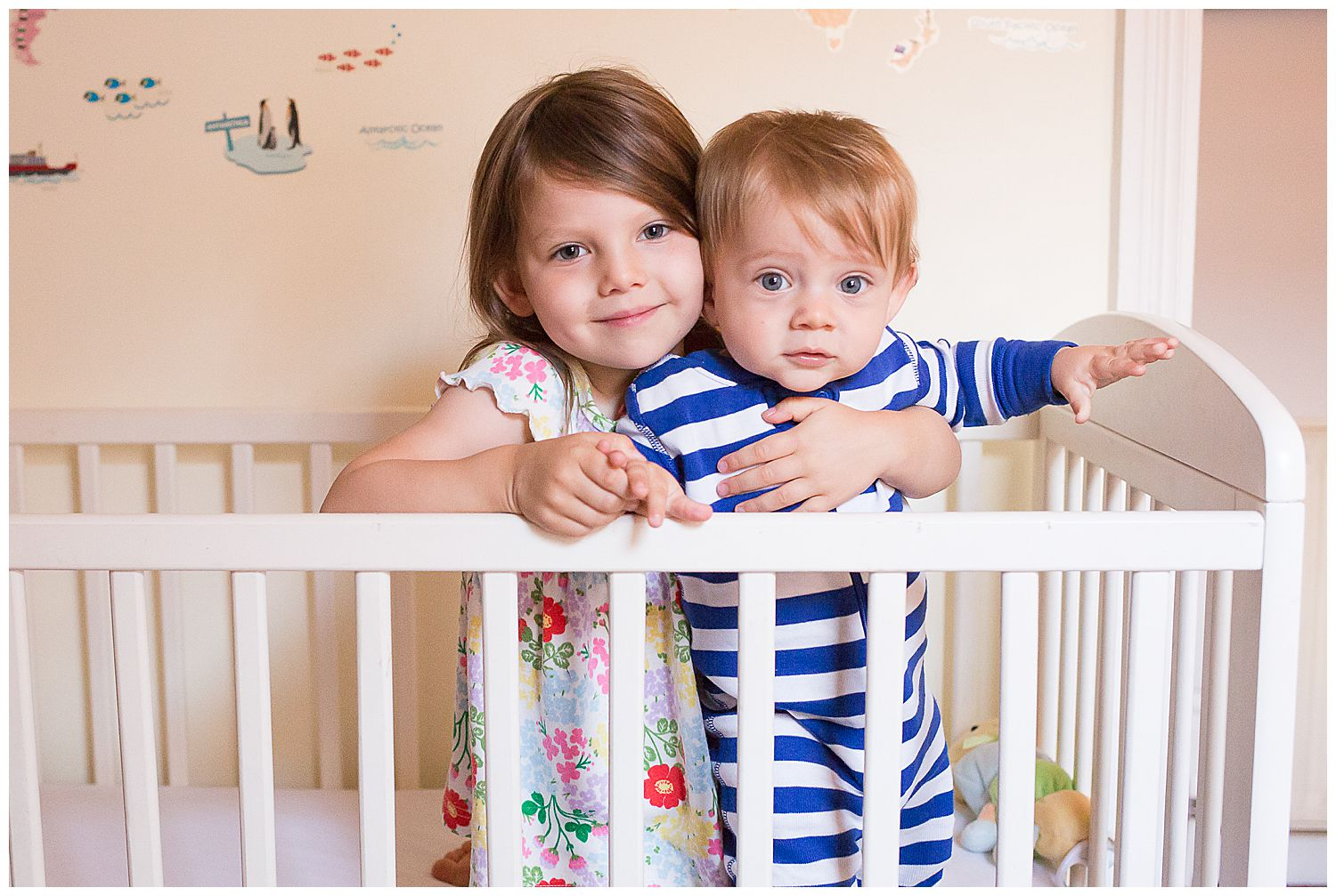 sister and brother hugging in cot