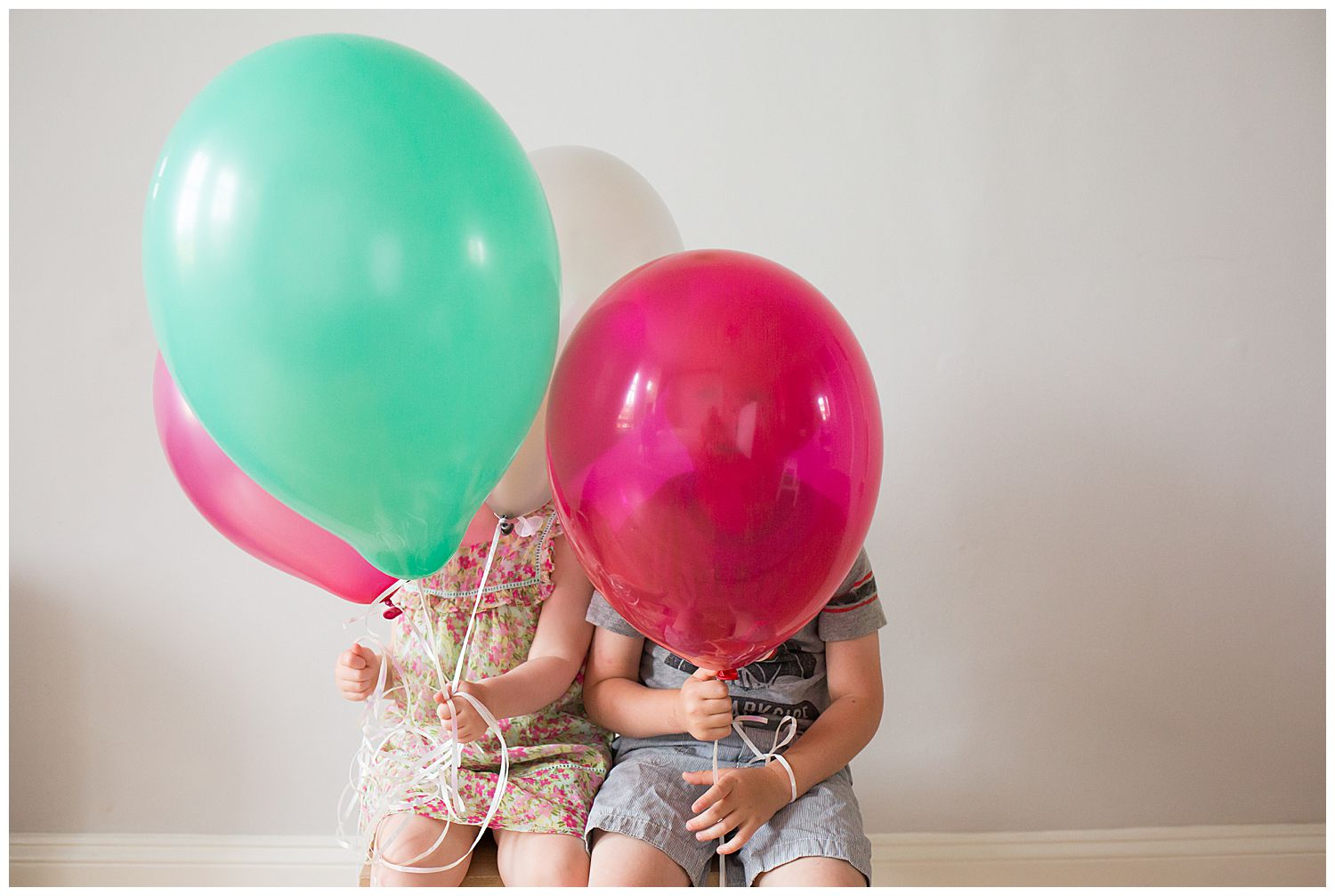 brother and sister hiding behind balloons