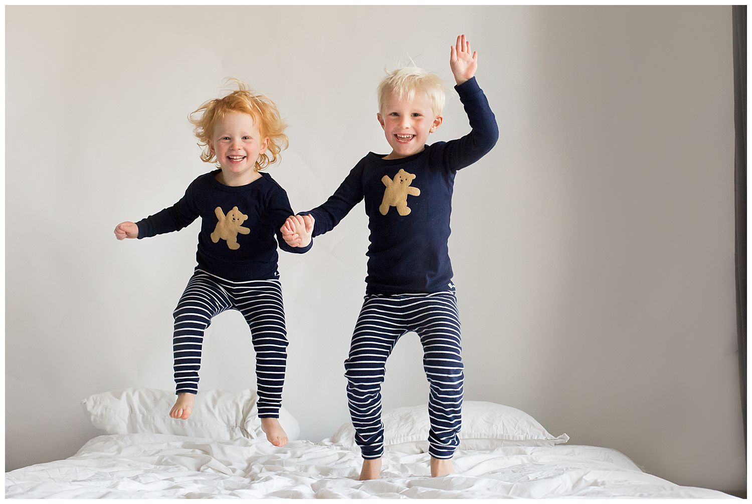 two siblings jumping on the bed