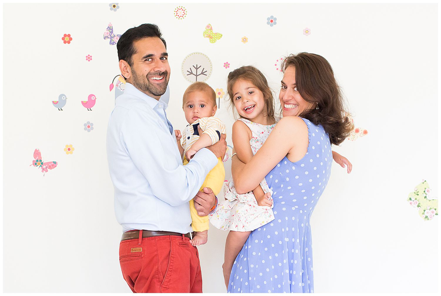 family of four against a butterfly wall