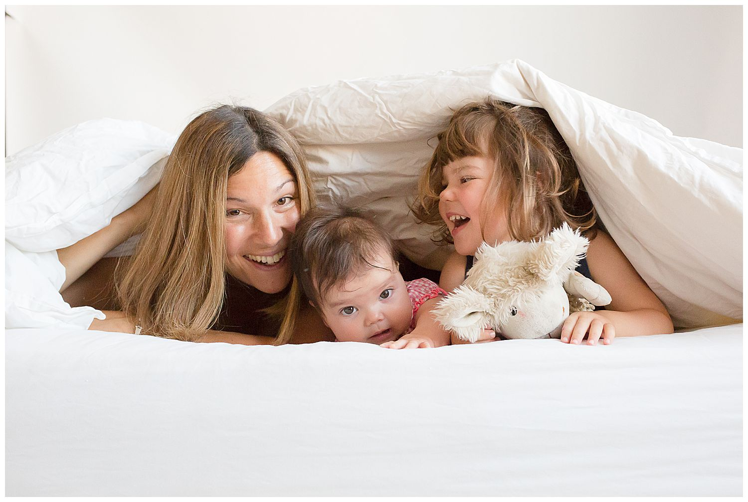 mum hiding under covers with two girls