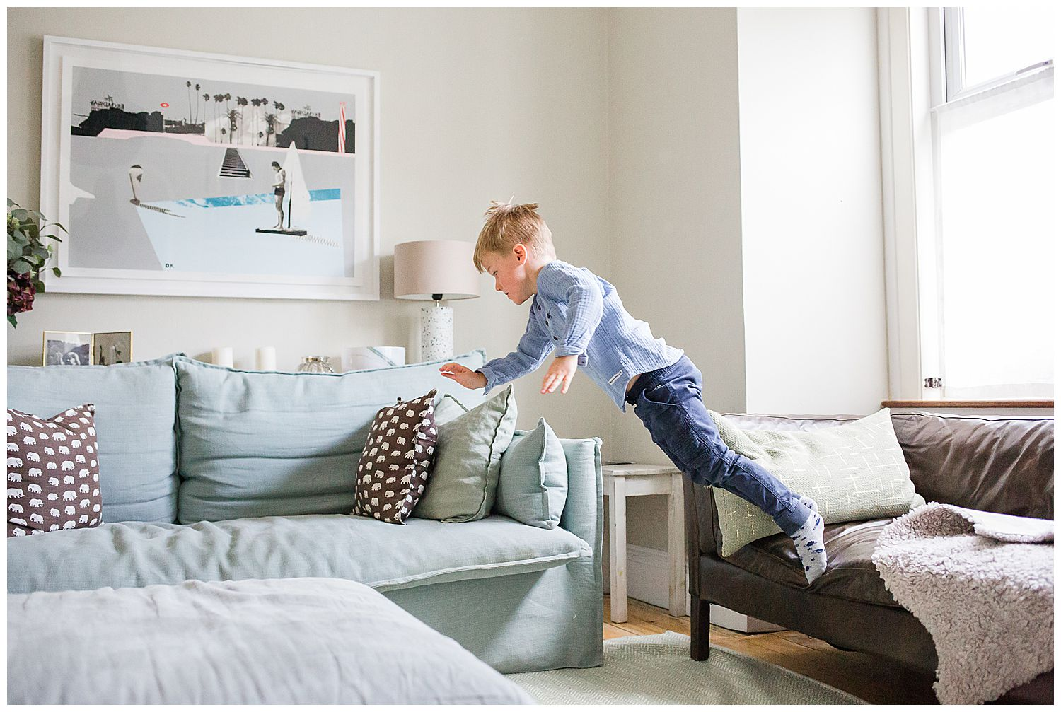 boy jumping from sofa to sofa