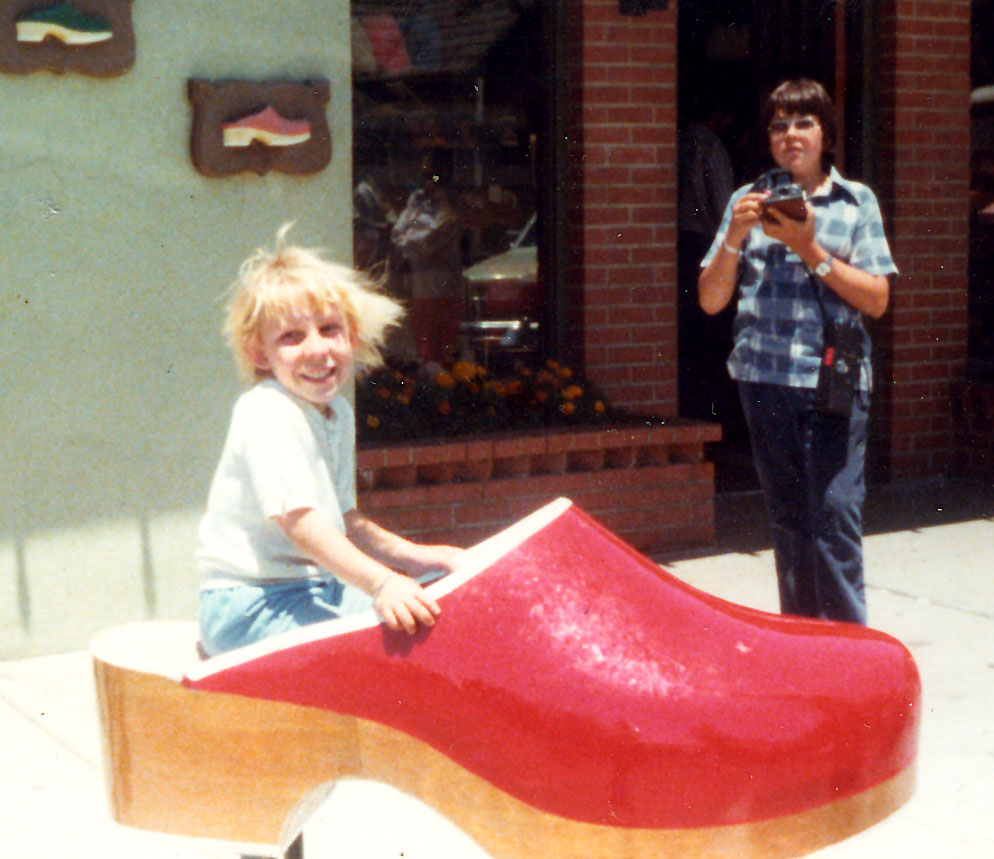My sister sitting in Solvang shoe store's wooden shoe in 1977