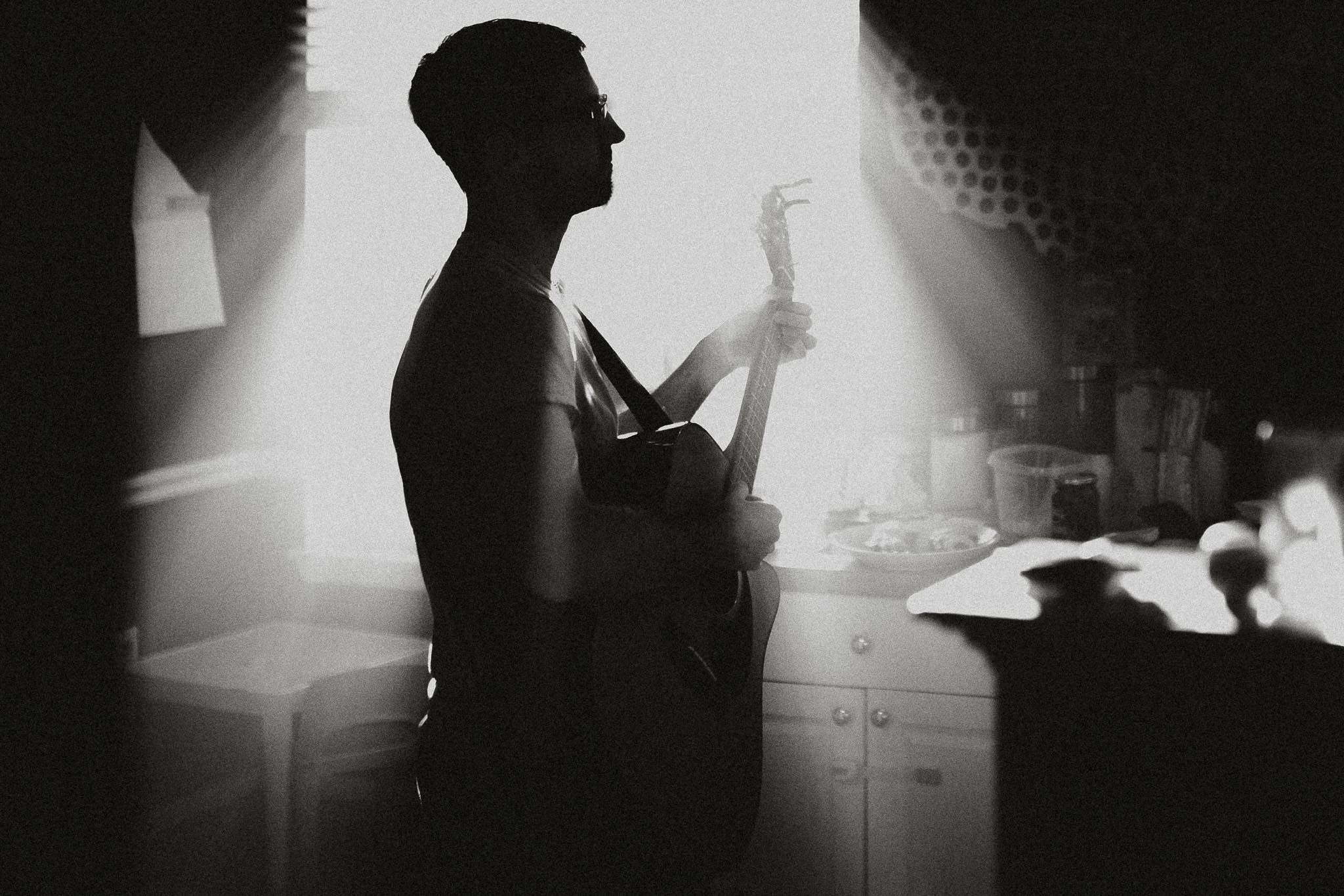 Black and white silhouette of a man playing guitar in a room filled with sun beams