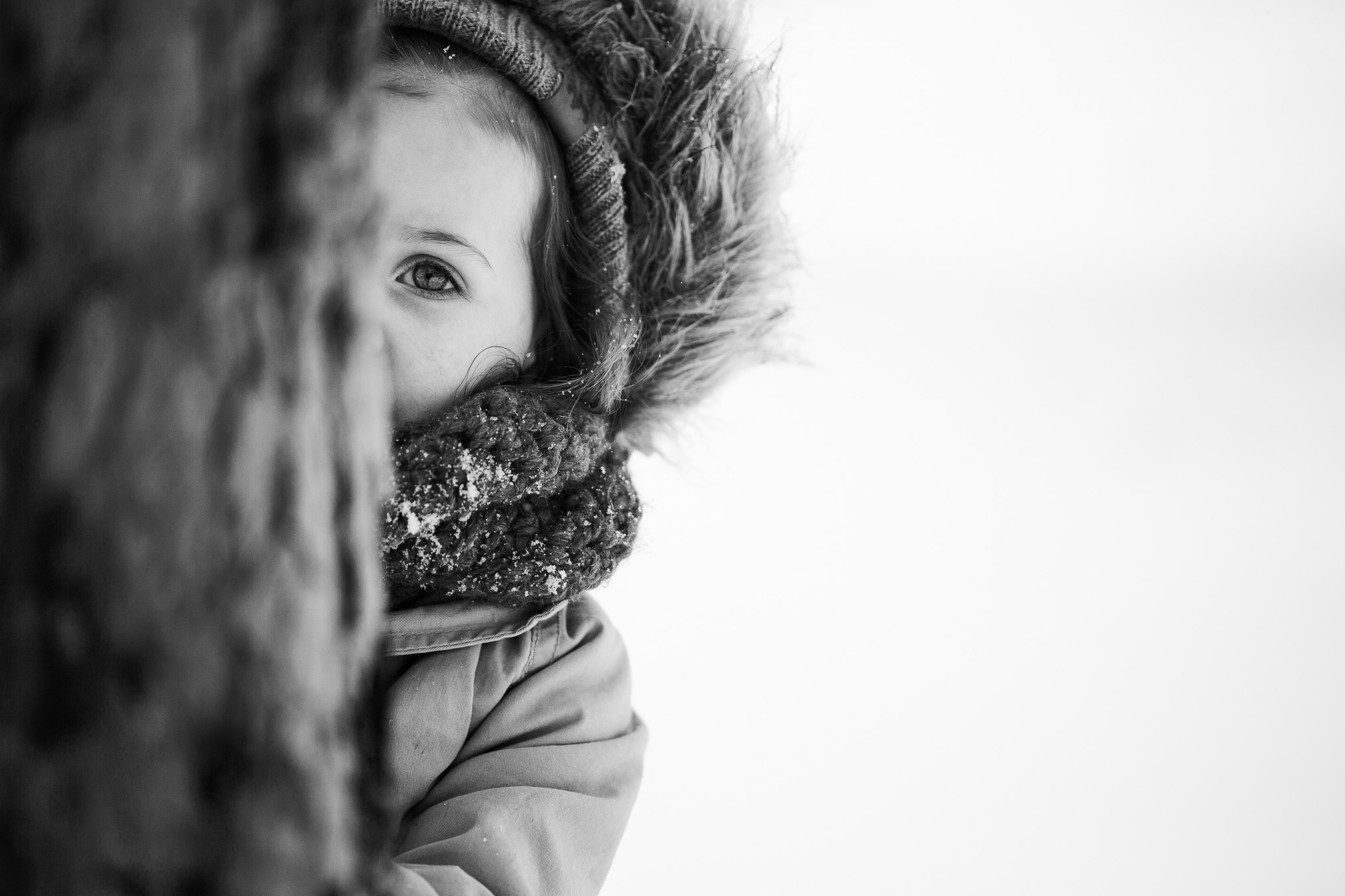 Black and white portrait of a toddler hiding behind a tree