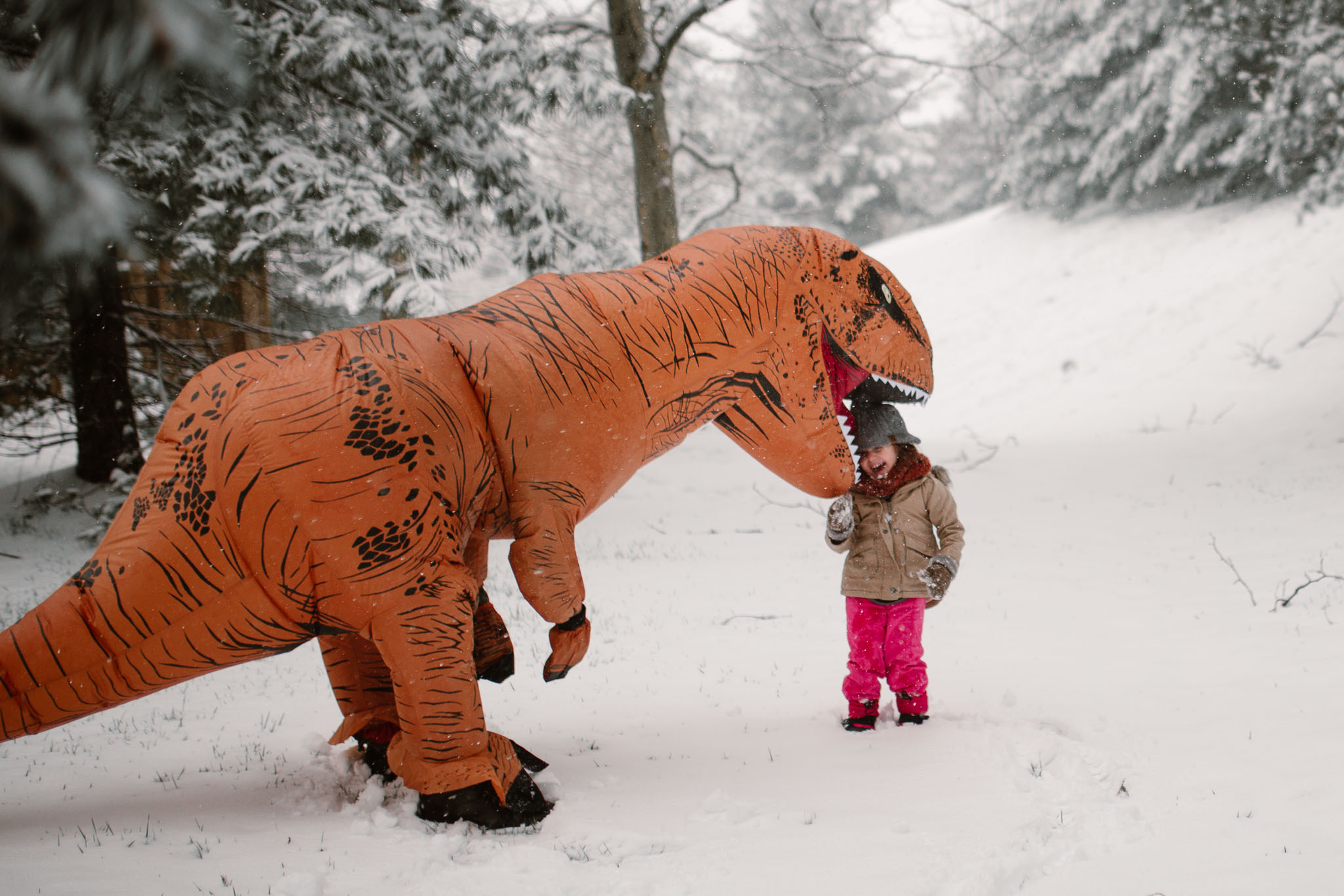 An orange dinosaur pretends to eat a toddler while they play outside in the snow