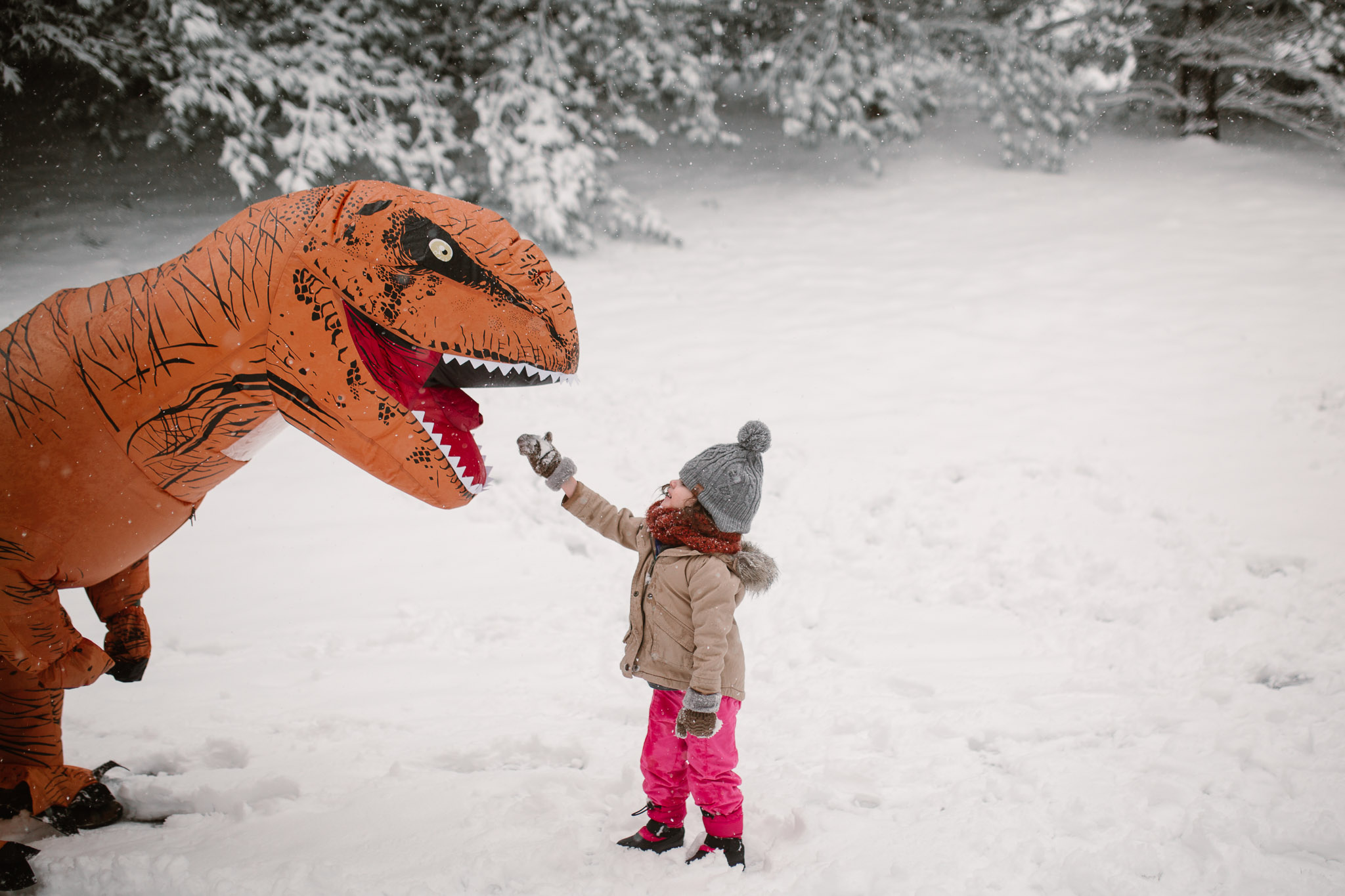 A toddler attempts to feed an orange dinosaur as they play outside in the snow