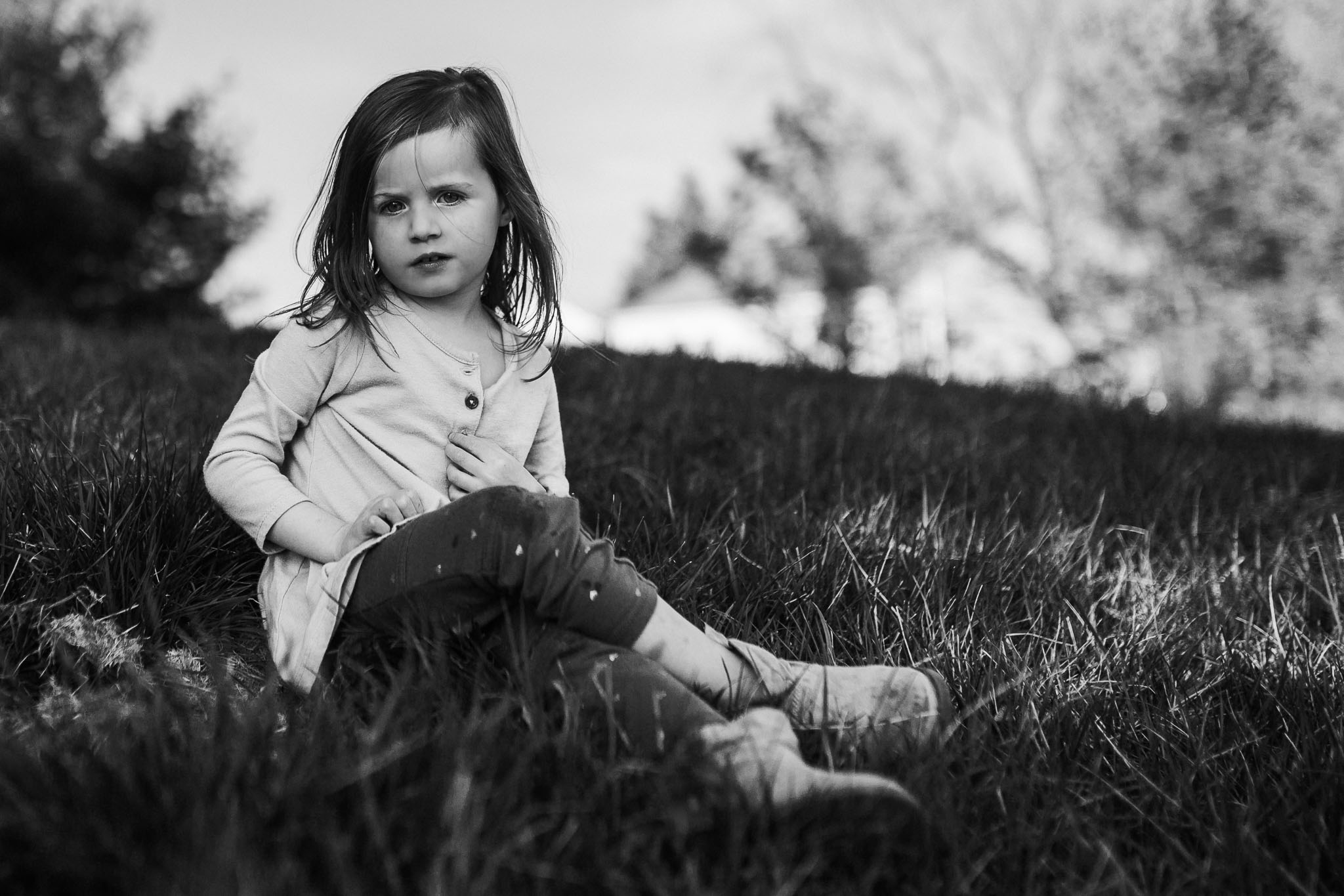 Black and white portrait of a girl sitting in a grassy field
