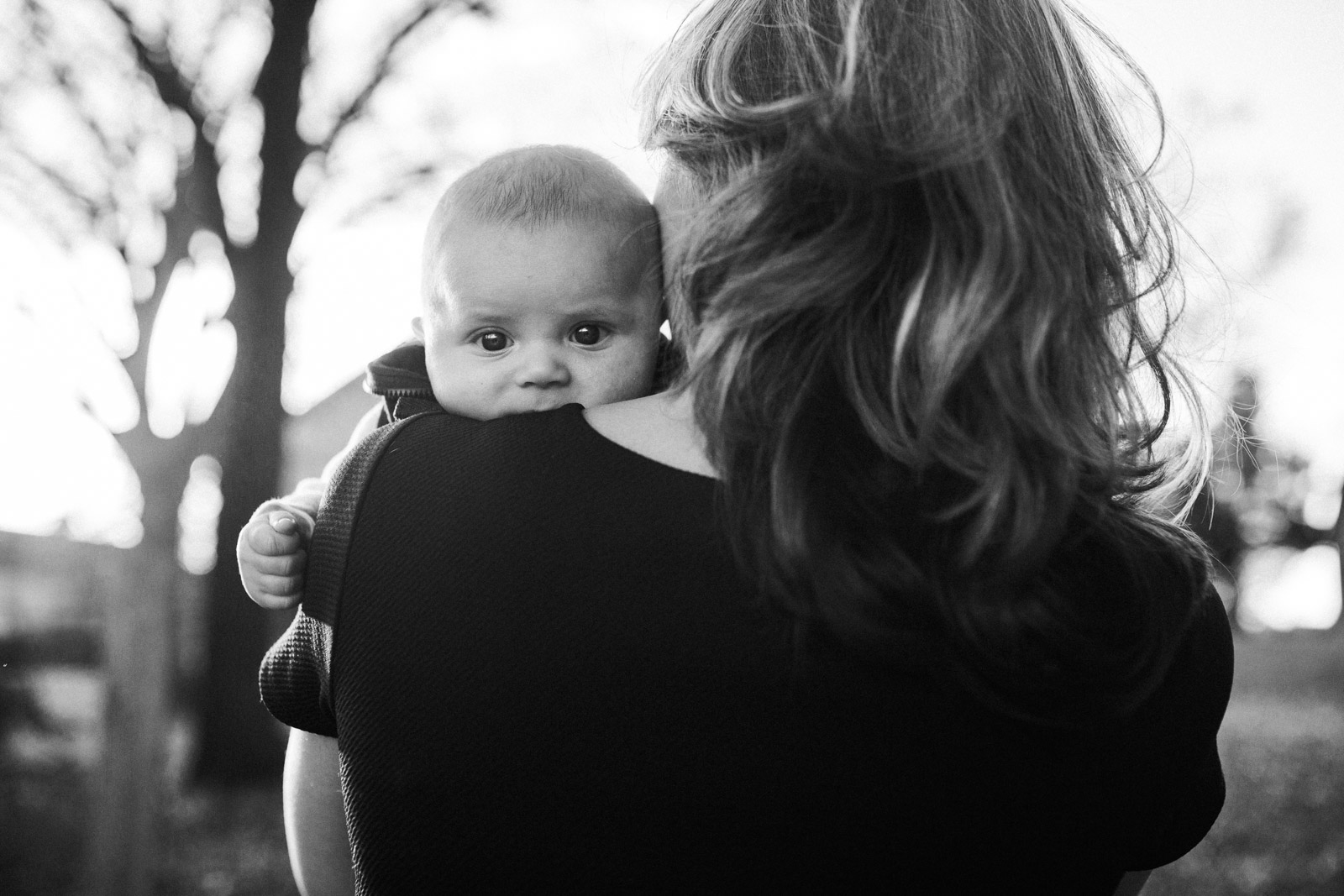Black and white; baby boy looking over his mom's shoulder; Claude Moore Park, Sterling, VA