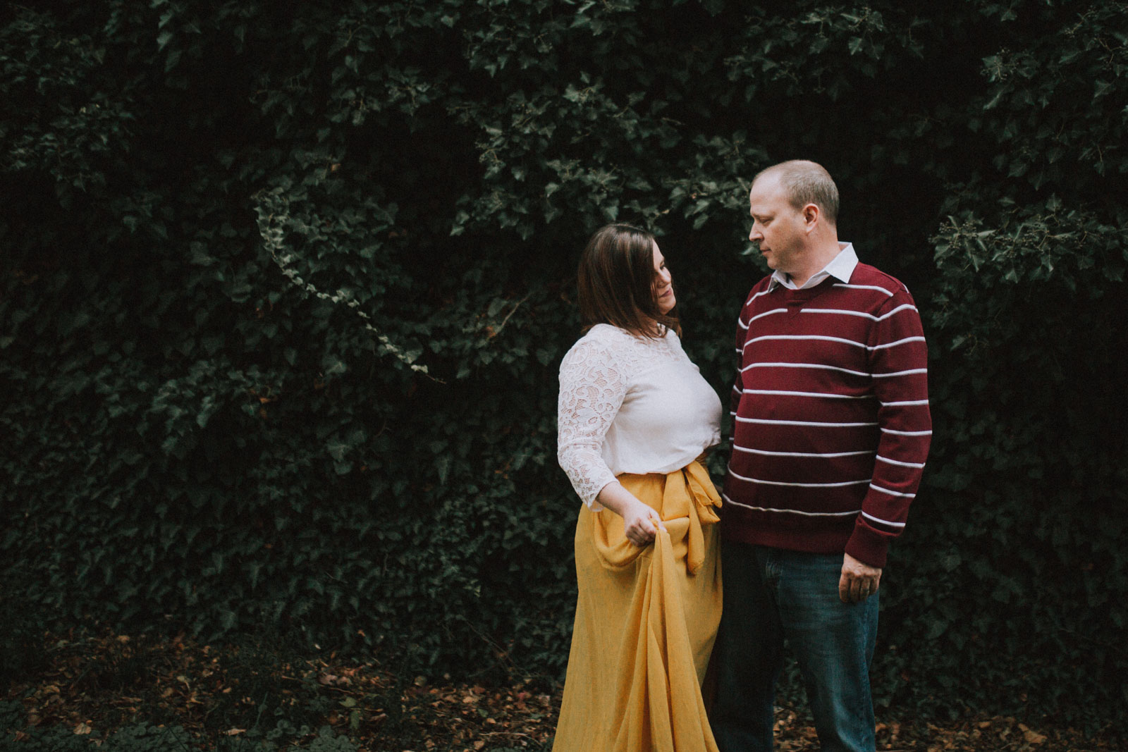 Couple stands together near a wall covered in ivy; Downtown Leesburg Virigina