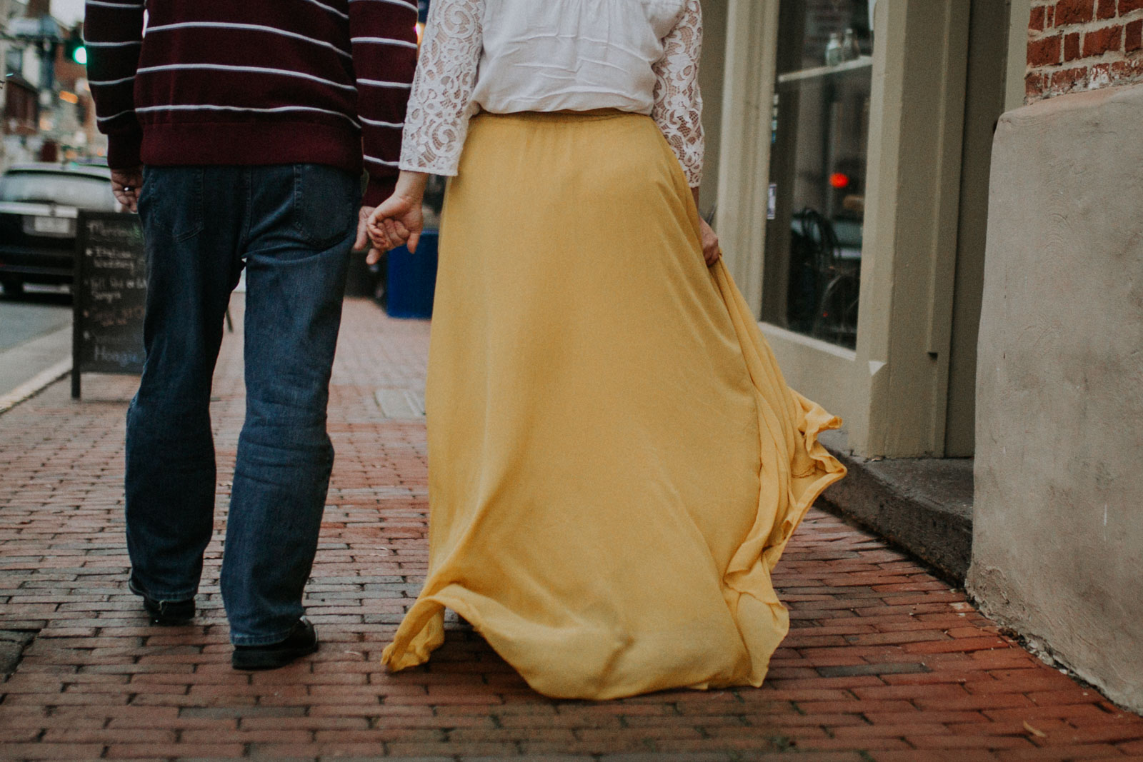 Woman in a yellow skirt holds hands with her husband as they walk down a brick siddewalk;  Downtown Leesburg Virigina