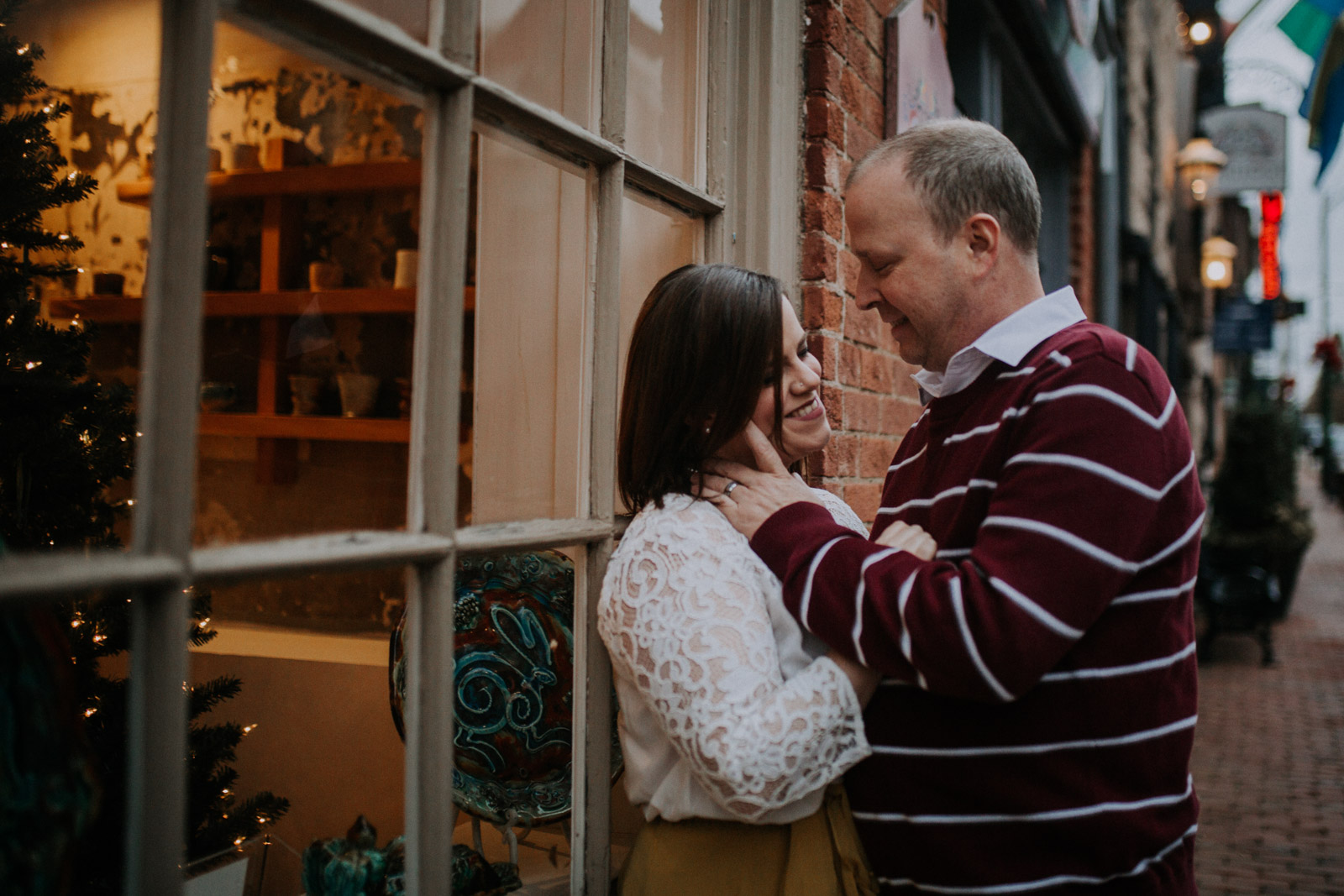 Couple leans against a store window decorated for Christmas;  Downtown Leesburg Virigina