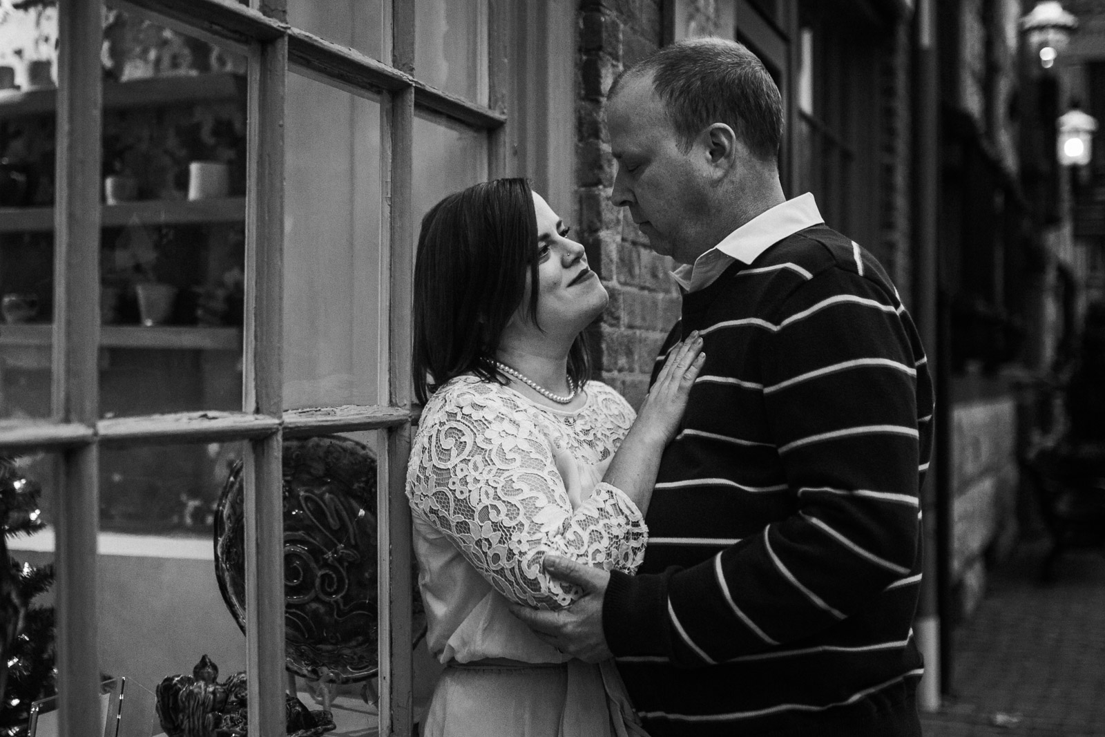 Black and white; couple stands near a store window decorated for Christmas;  Downtown Leesburg Virigina