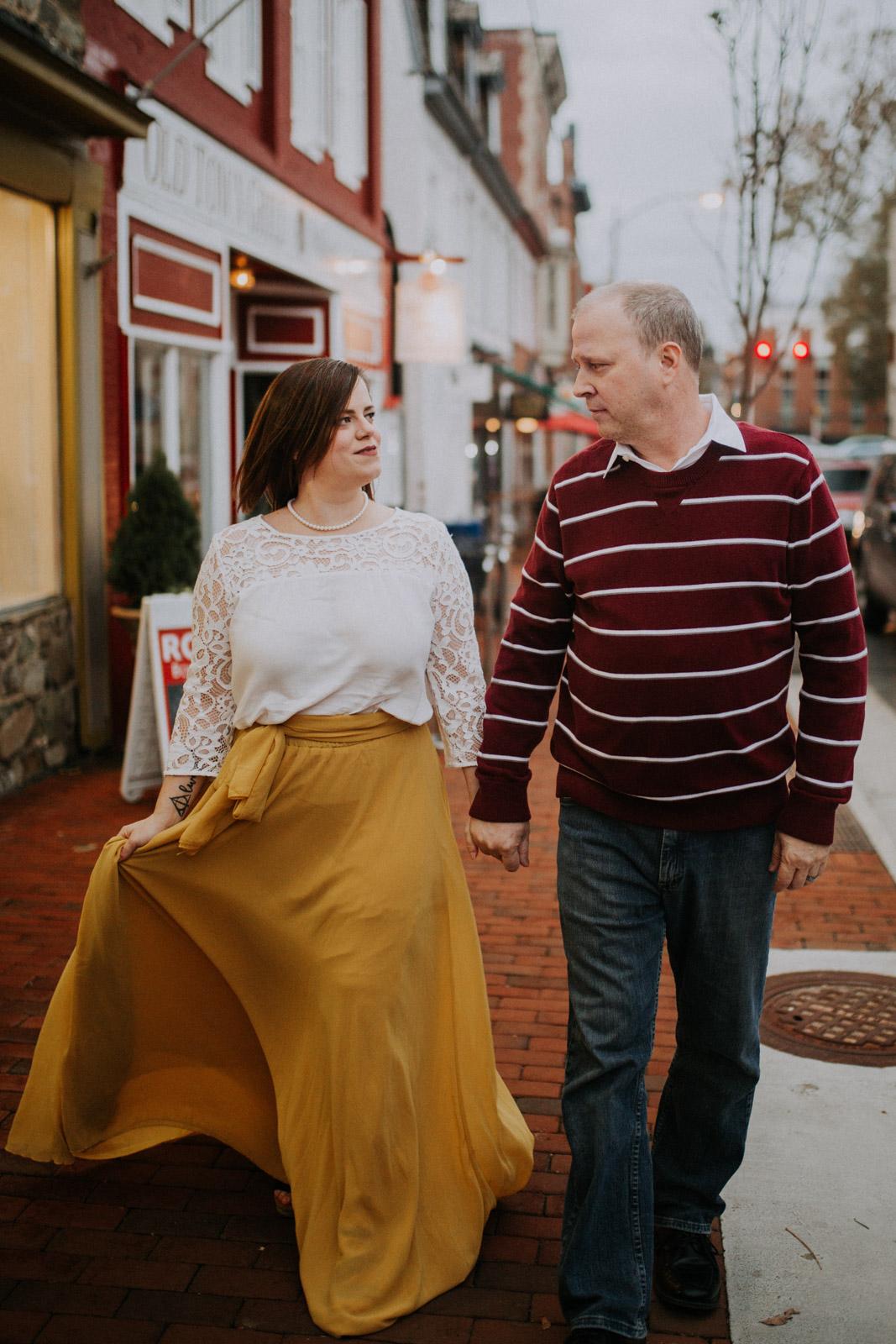 Couple holds hands and walks down the sidewalk of  Downtown Leesburg Virigina