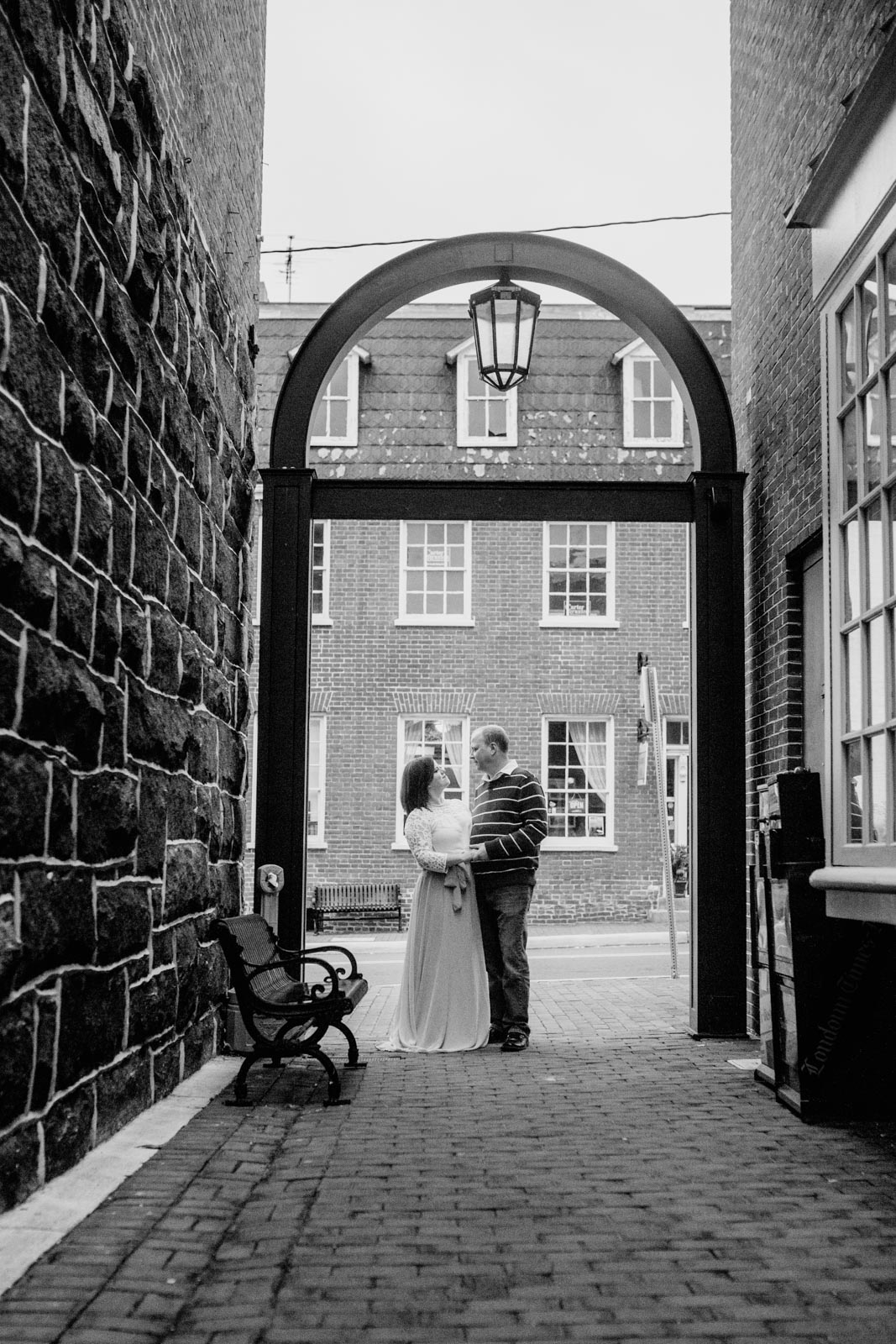 Black and white; couple stands under an arch in  Downtown Leesburg Virigina