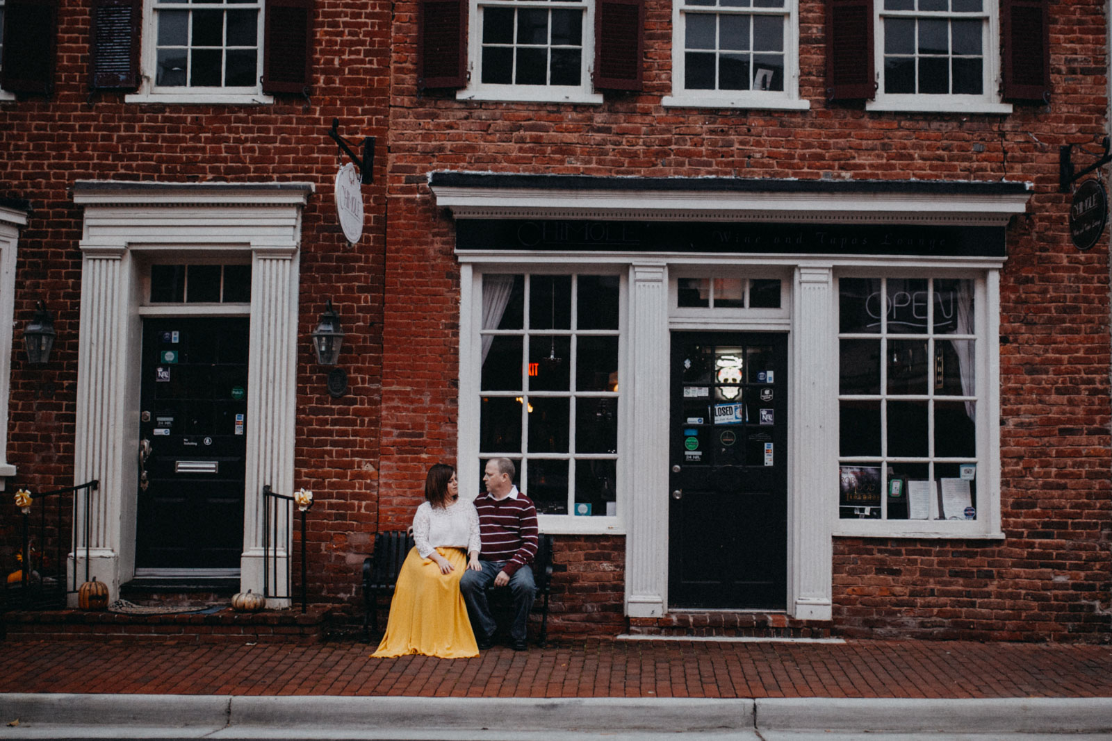 Couple sits on a bench in front of a brick building in  Downtown Leesburg Virigina
