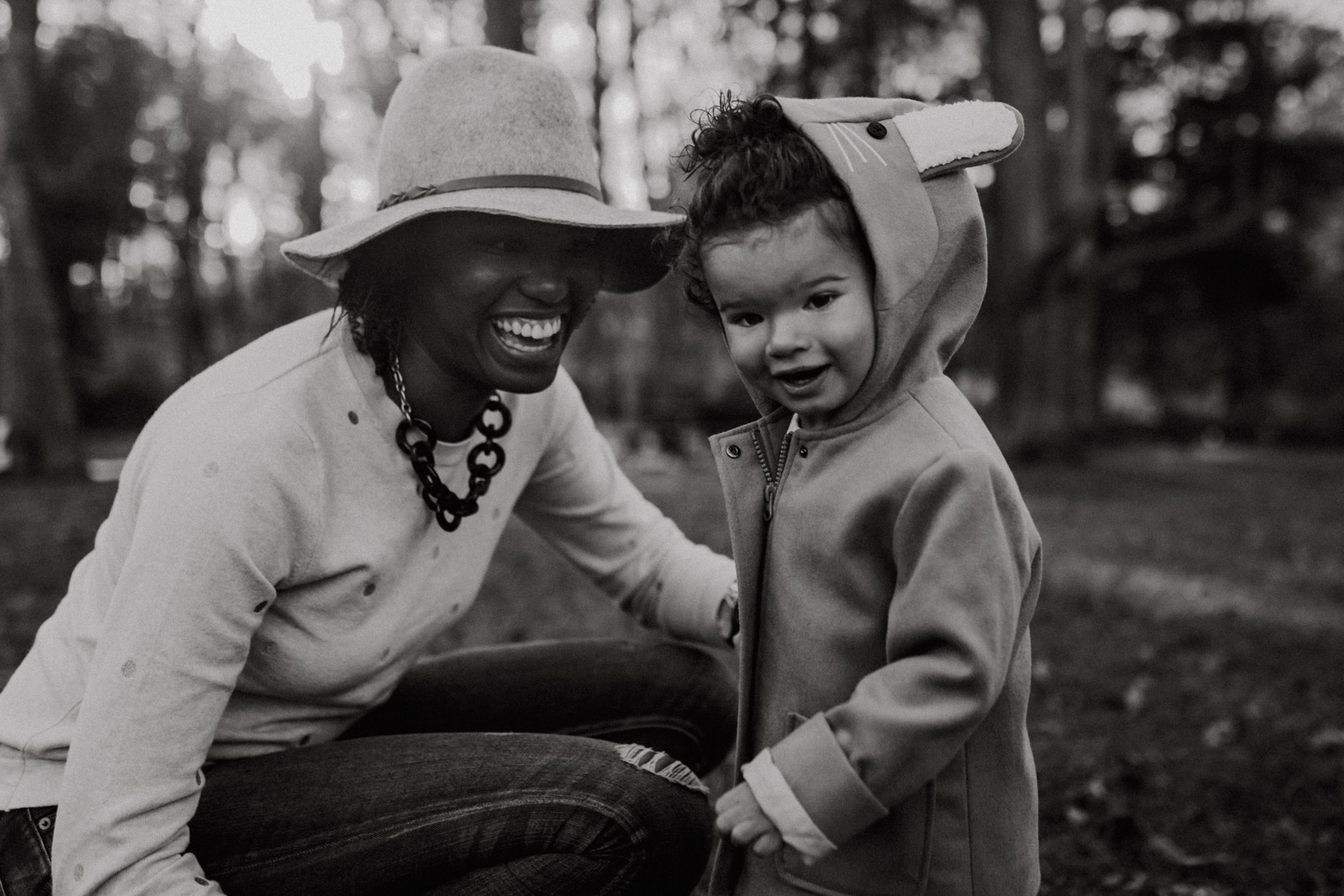 Black and white; mom laughs at her toddler daughter who is staring at the viewer at  at Ellanor C. Lawrence Park in Chantilly, Virginia