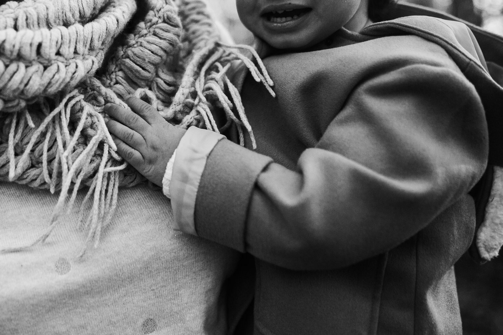 Black and white; toddler holds tightly to her mom's scarf  at Ellanor C. Lawrence Park in Chantilly, Virginia