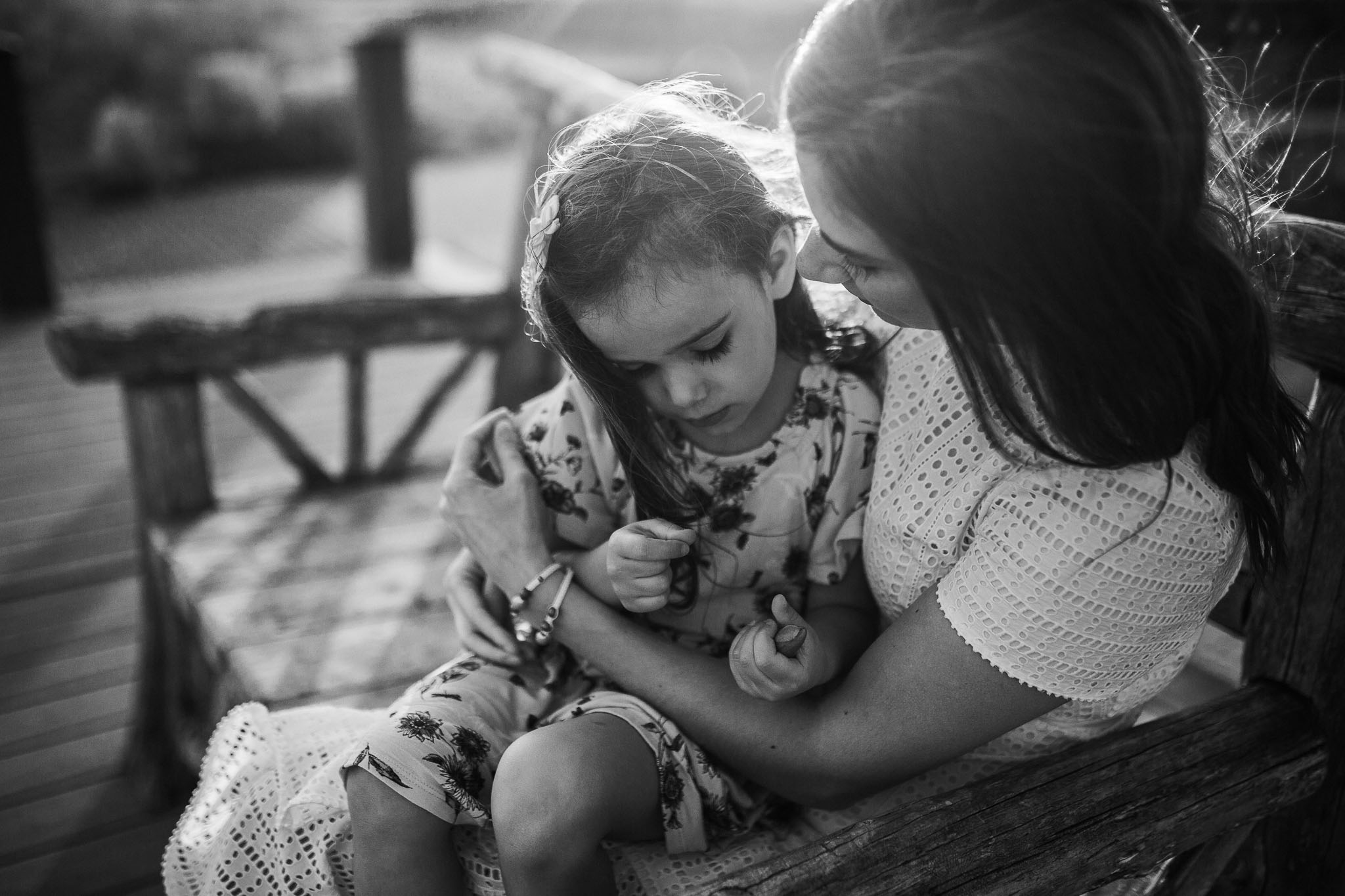 Black and white; mother and daughter snuggle together on a bench at sunset at Willowsford Boat House Aldie, VA