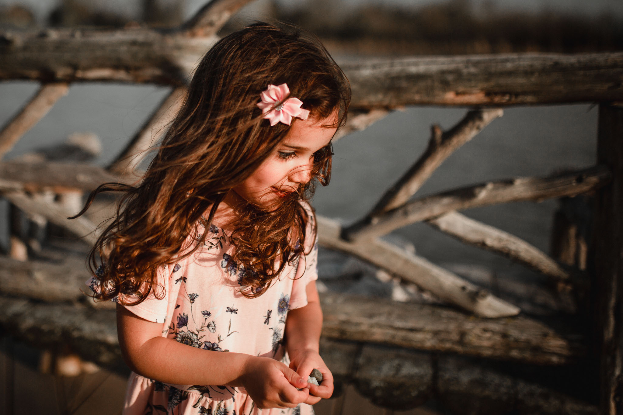 Girl in a pink dress with a flower in her hair holding a handful of rocks at Willowsford Boat House Aldie, VA