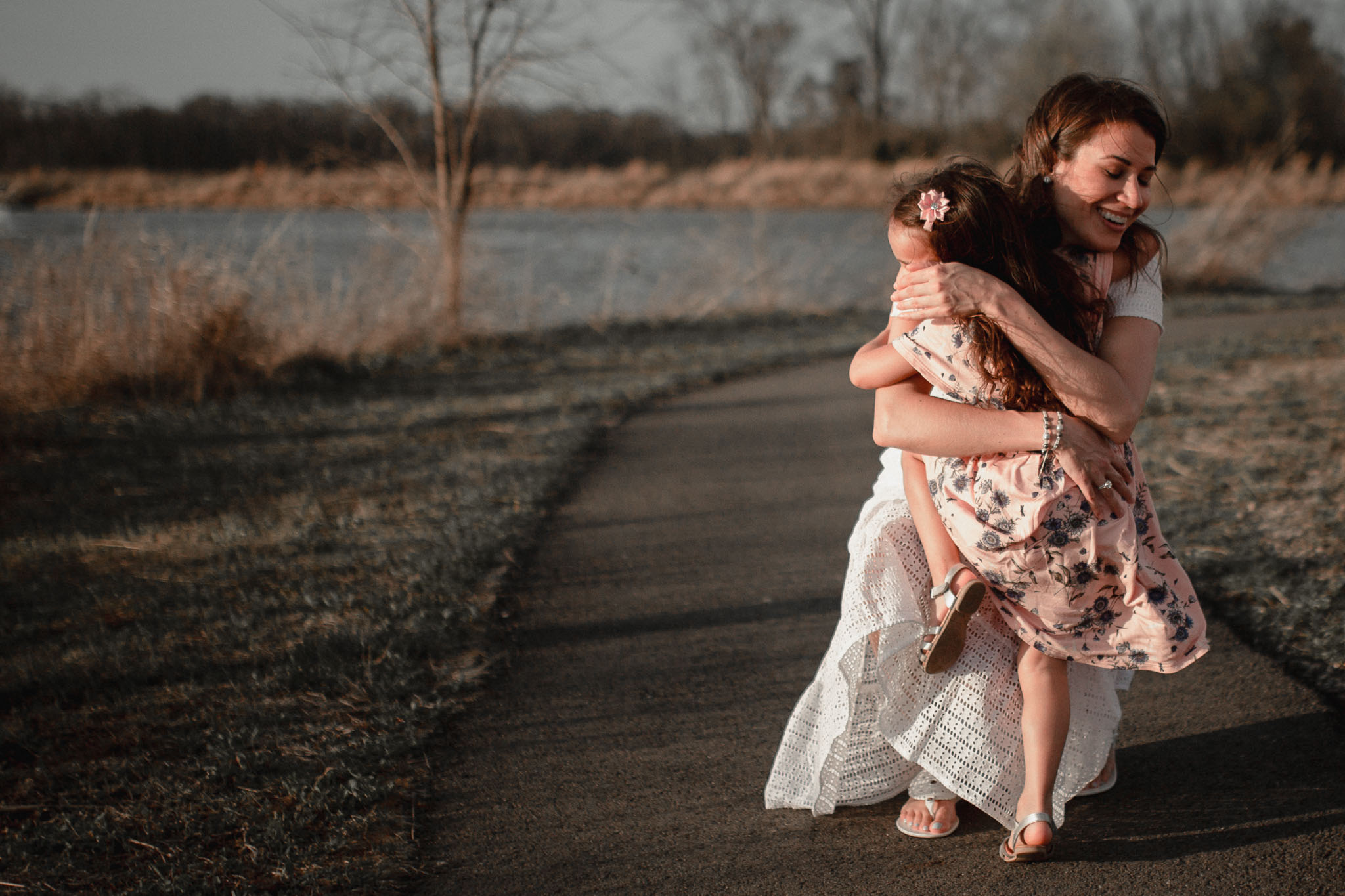 Girl in a pink dress runs to who mother who wraps her up in a big hug at Willowsford Boat House Aldie, VA
