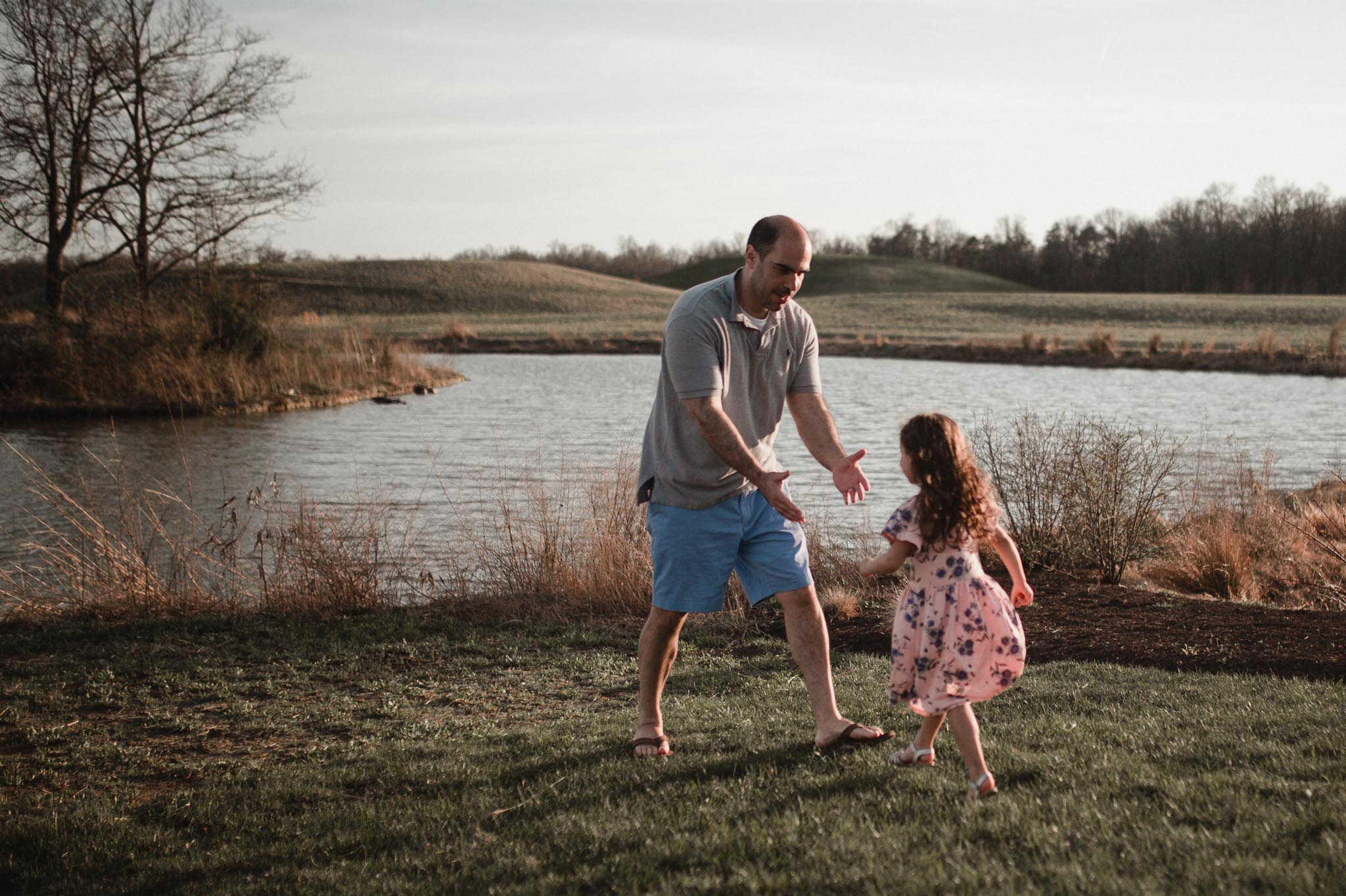 Girl in a pink floral dress runs to who dad who has his hands outstretched to catch her at Willowsford Boat House Aldie, VA