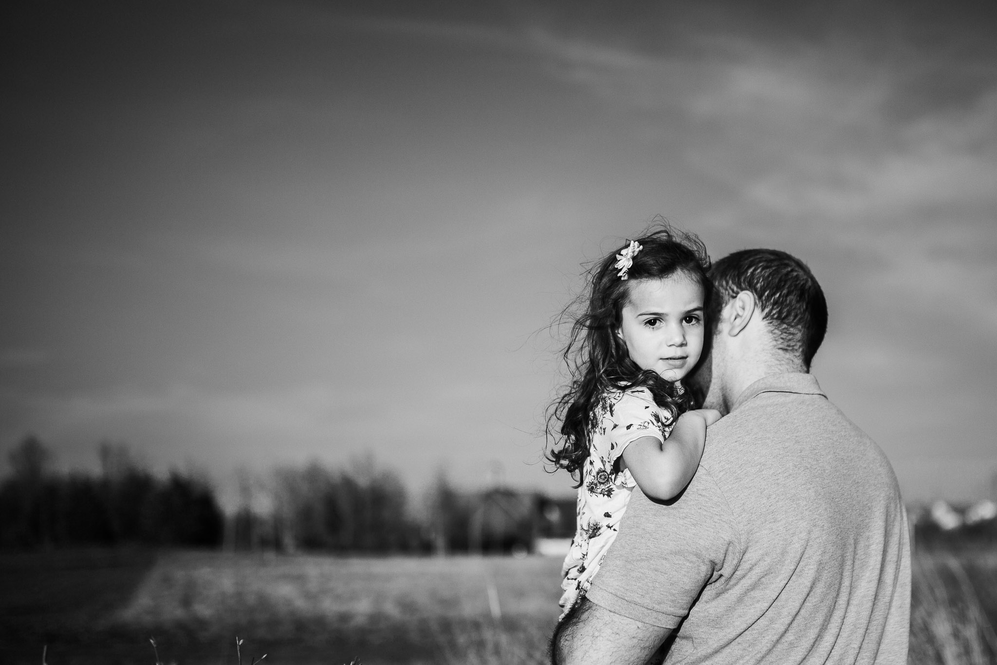 Black and white; dad holding his daughter as she looks over his shoulder at Willowsford Boat House Aldie, VA