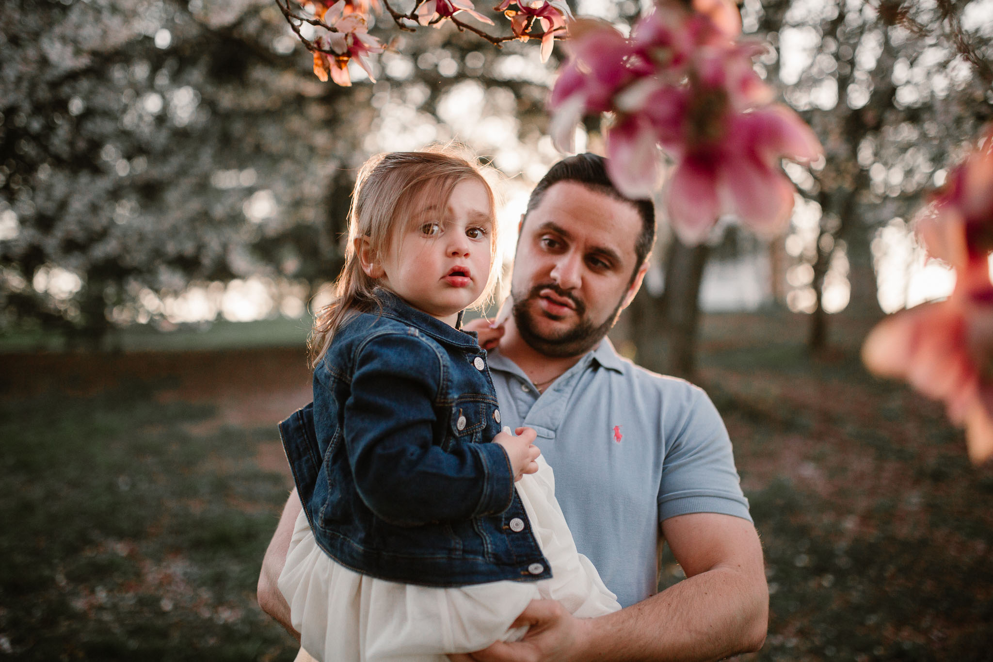 Father holds his daughter as she looks at the pink flowers on a tree  at Ida Lee Park in Leesburg, VA