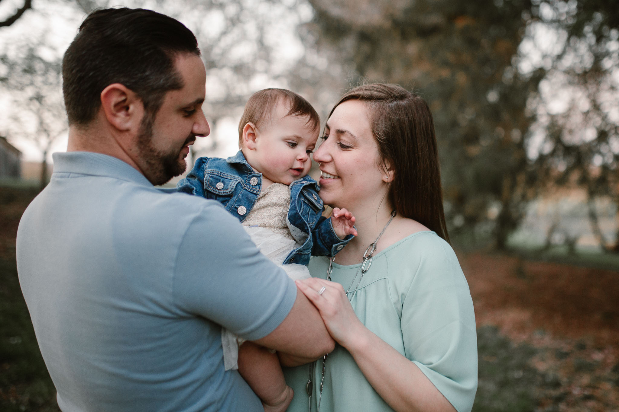 Parents hold and kiss their infant daughter  at Ida Lee Park in Leesburg, VA