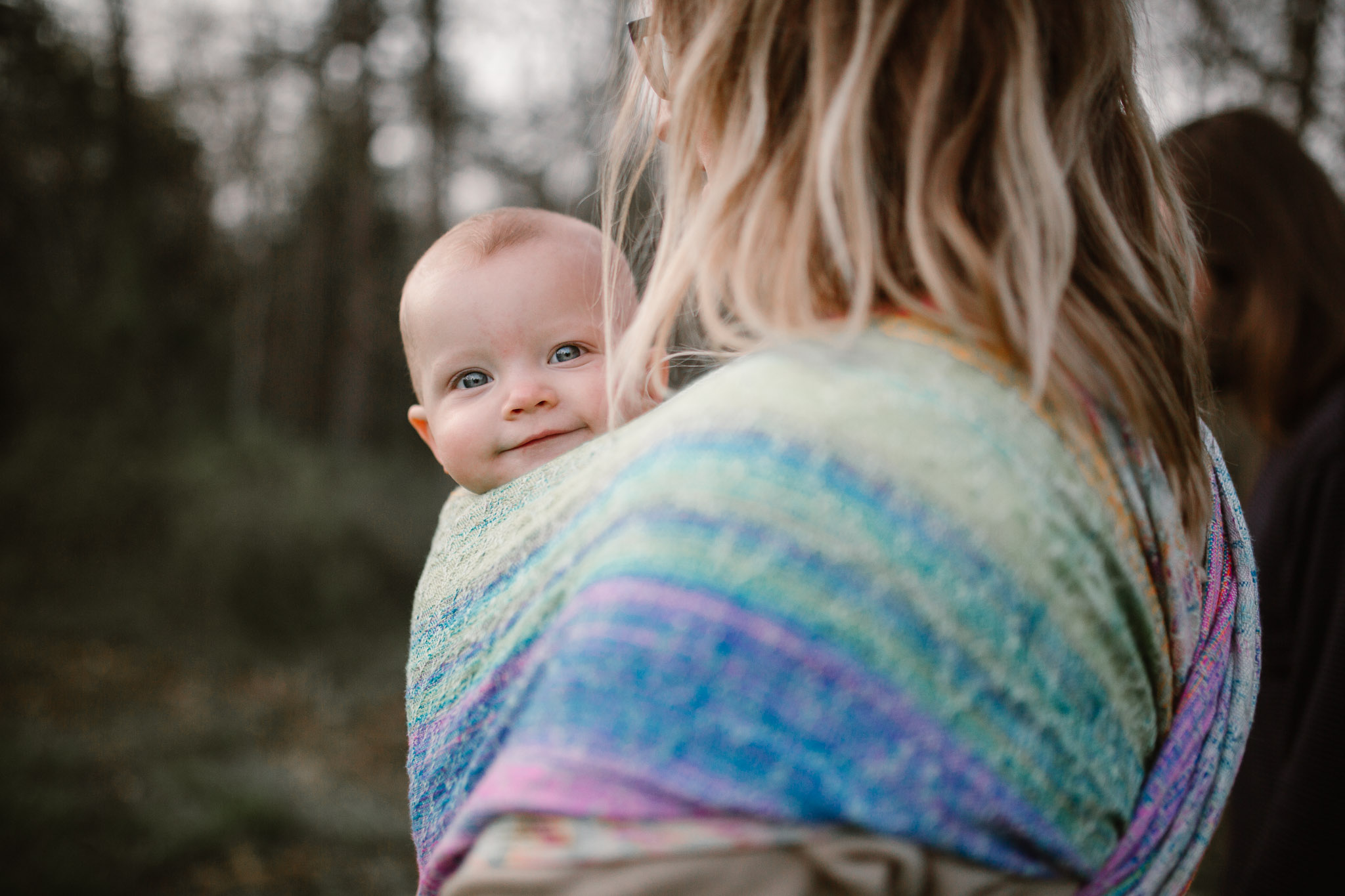 Baby girl in a rainbow carrier being held by her mom at Red Rock Overlook in Leesburg, VA
