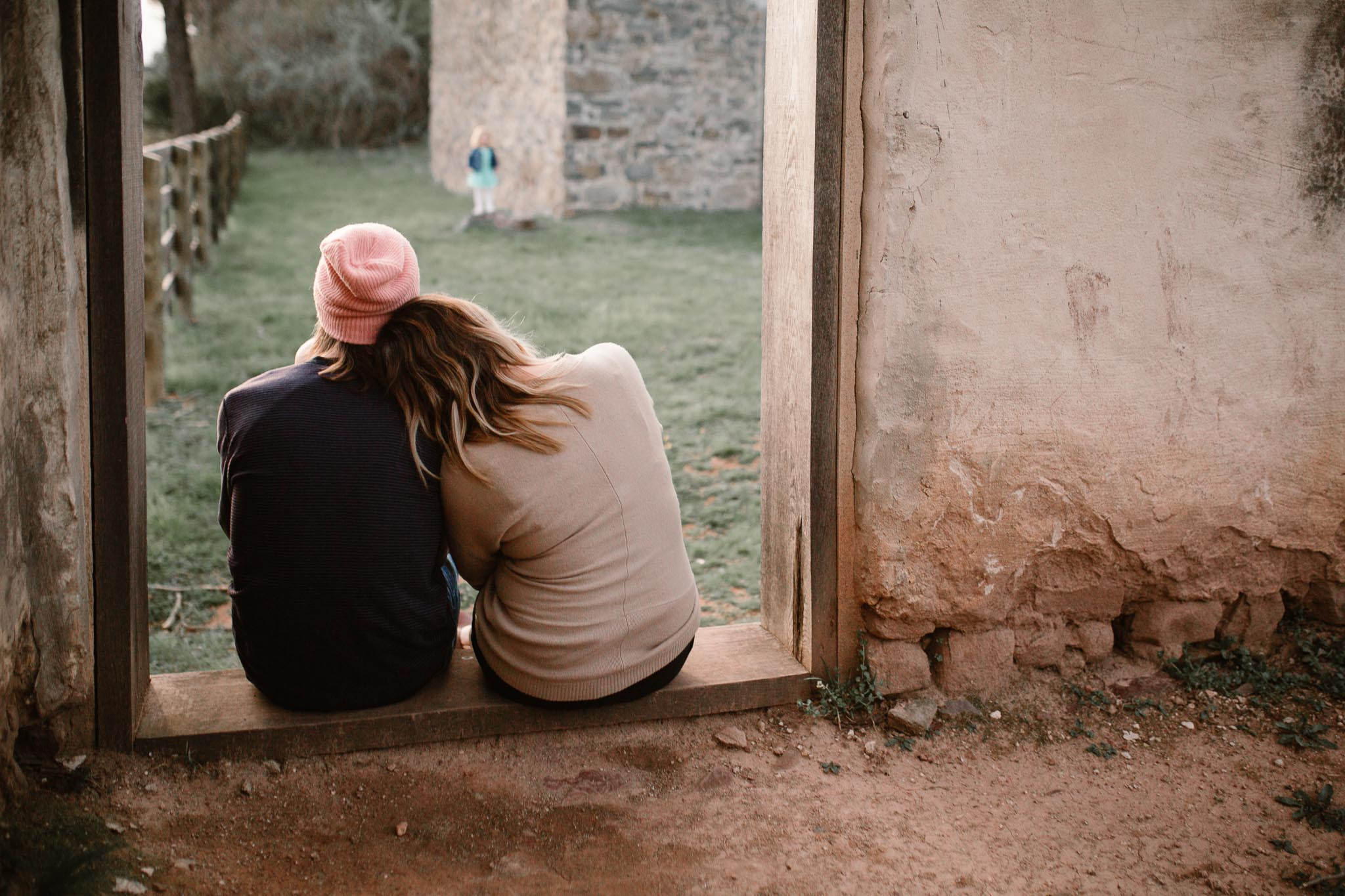 Couple sits together and watches their young daughter play at Red Rock Overlook in Leesburg, VA