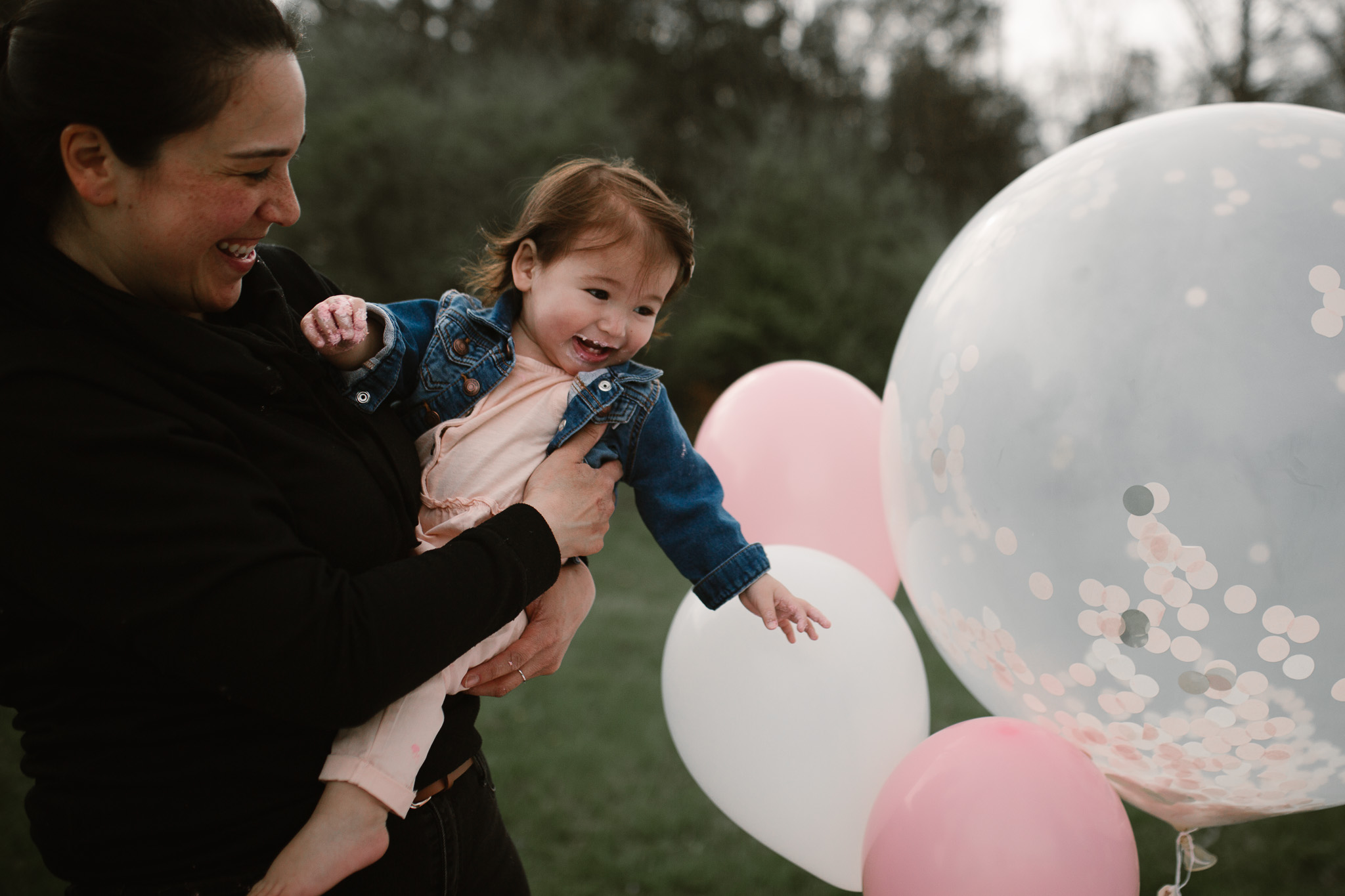 Mom holding her one year old little girl with icing on her face as she plays with her giant white and pink balloons at Red Rock Overlook in Leesburg, VA