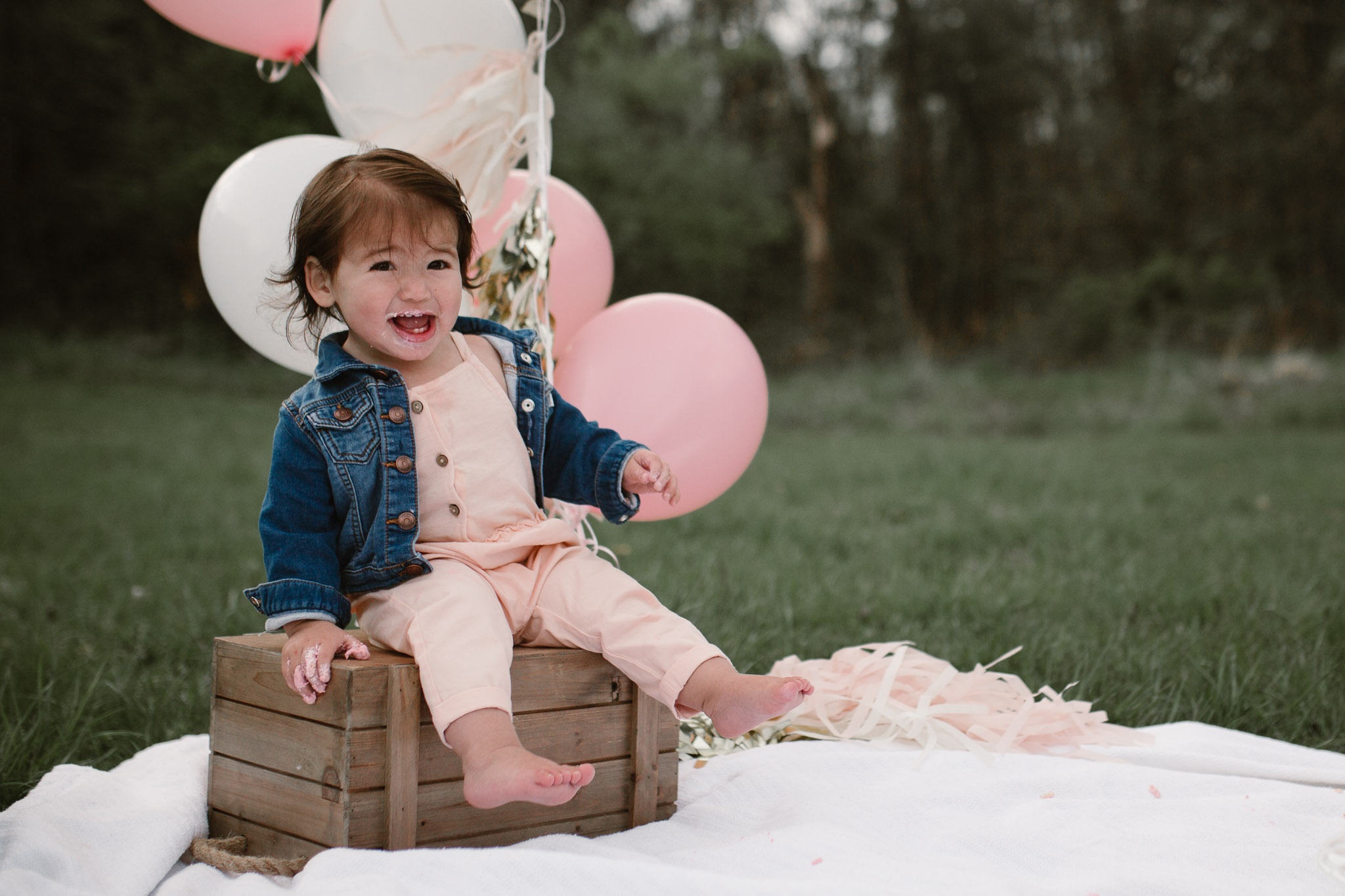 One year old birthday girl sits on a wooden crate with balloons behind her and icing on her hands and face at Red Rock Overlook in Leesburg, VA