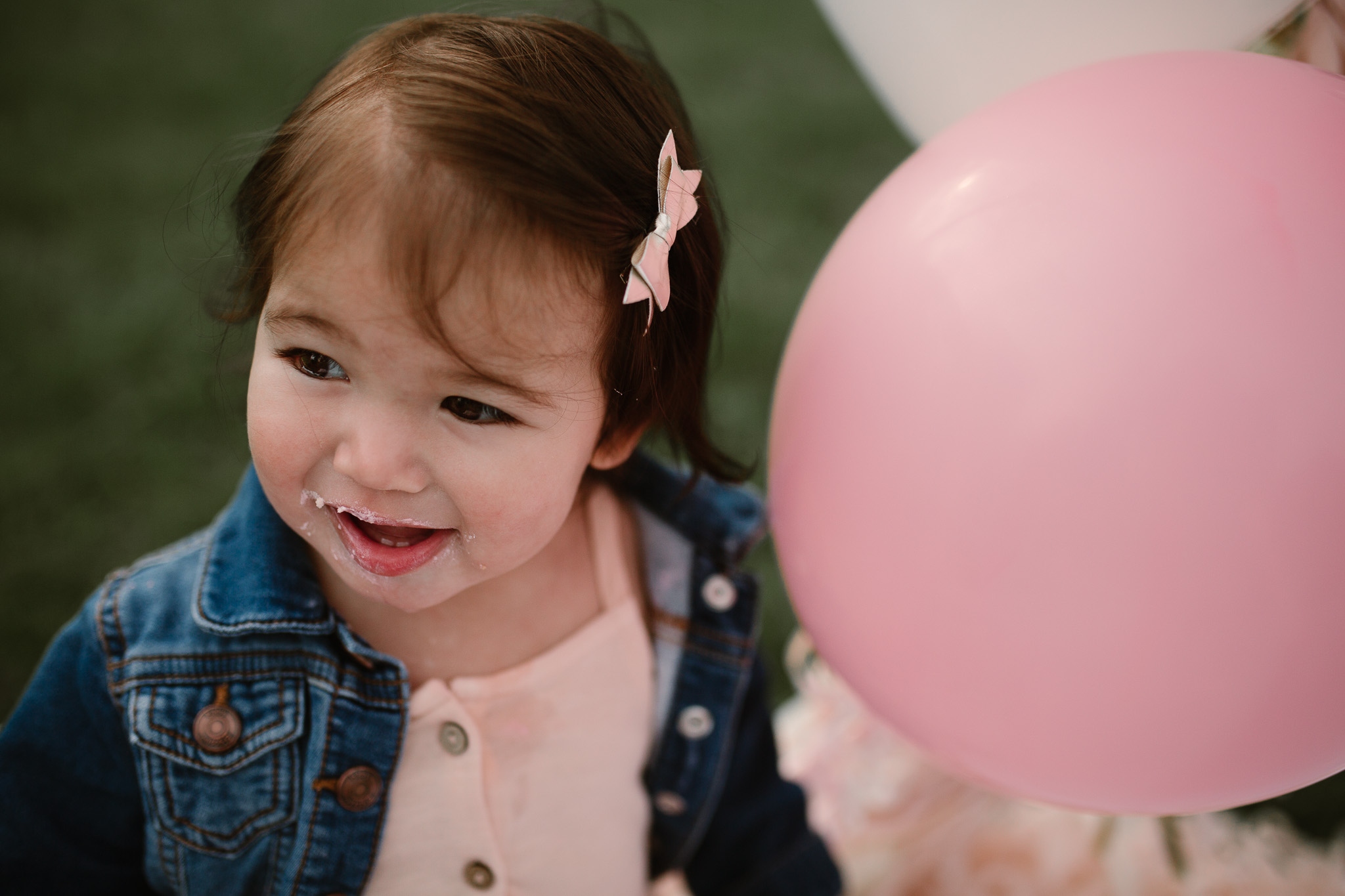 Close up of the one year old birthday girl with icing on her face and pink balloons next to her at Red Rock Overlook in Leesburg, VA