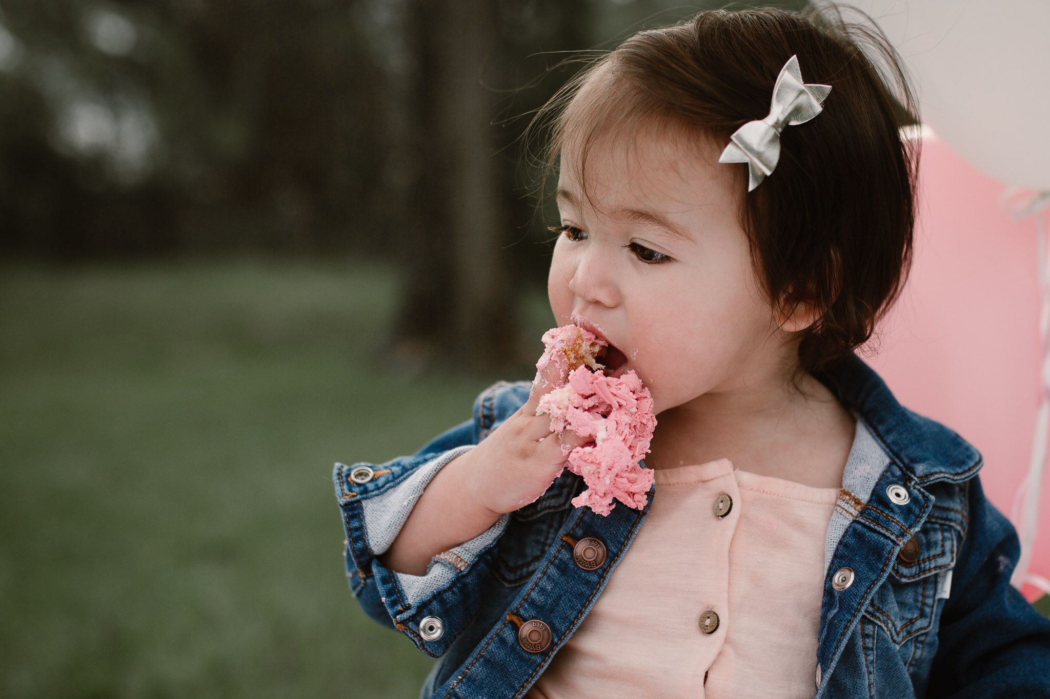 One year old birthday girl eating a fistful of pink icing at Red Rock Overlook in Leesburg, VA