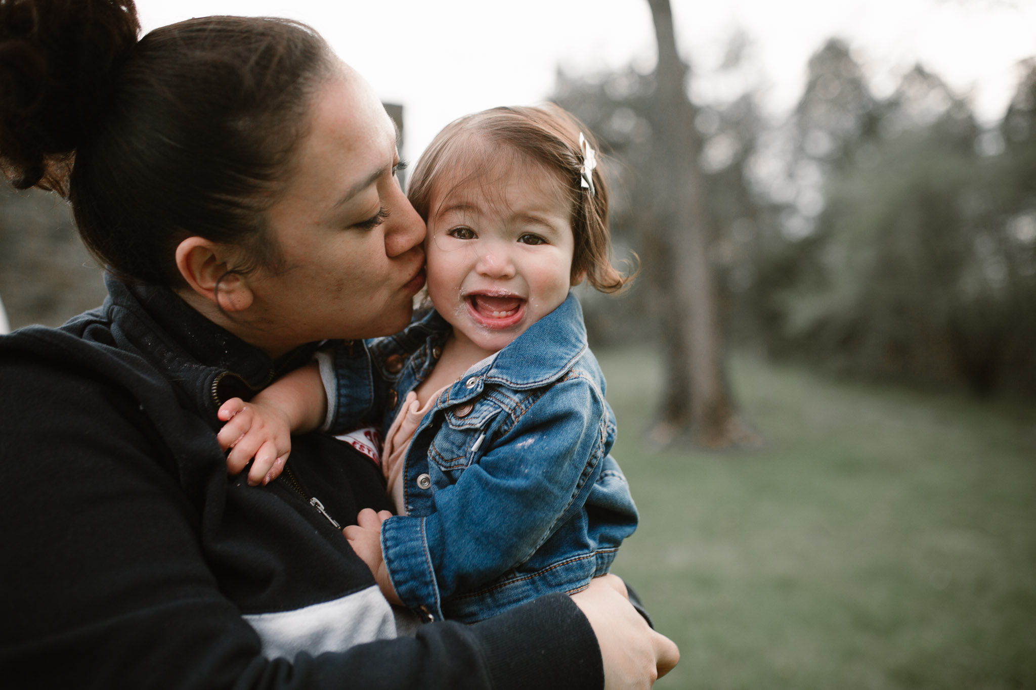 One year old girl makes a funny face as her mom gives her a kiss on the cheek at Red Rock Wilderness Overlook in Leesburg, VA.