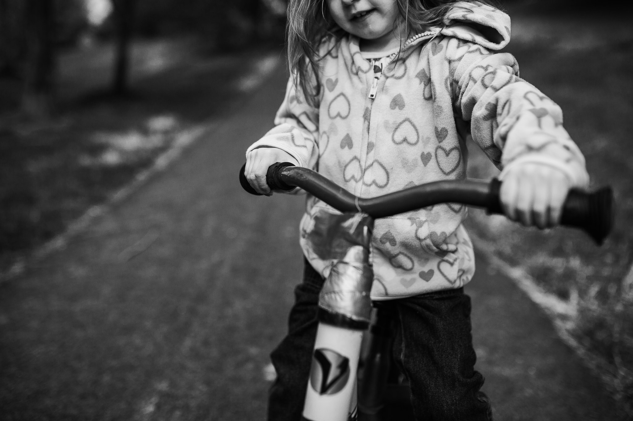 Black and white close up of a girl in a heart hoodie riding a bike in Ashburn, Virginia