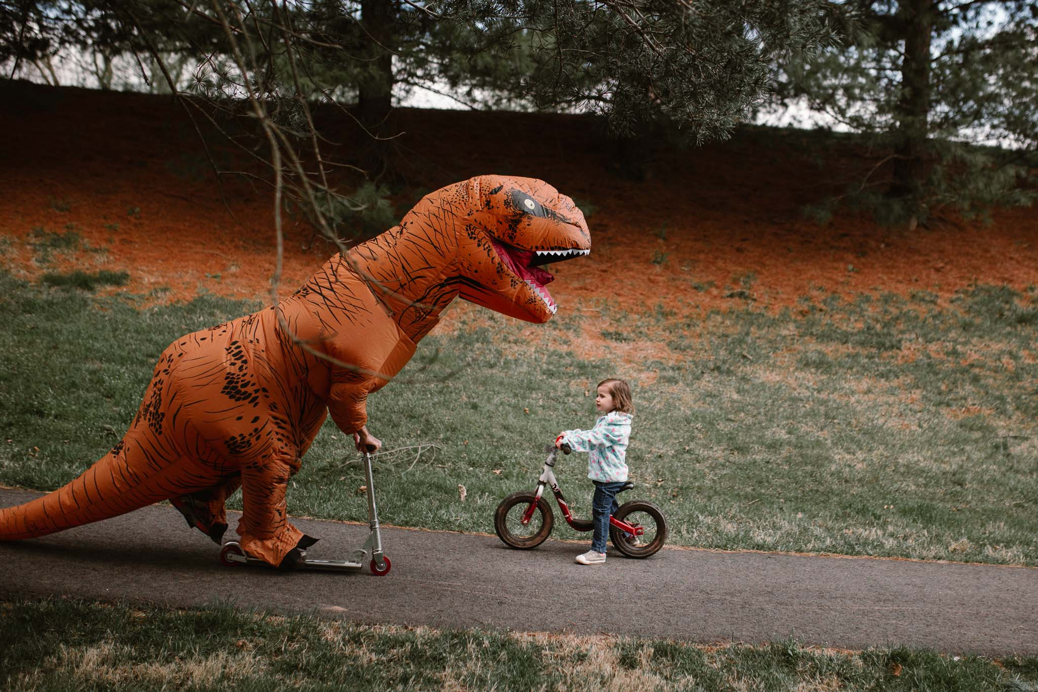 Girl on a bike and dinosaur on a scooter ride toward each other on a path in Ashburn, Virginia