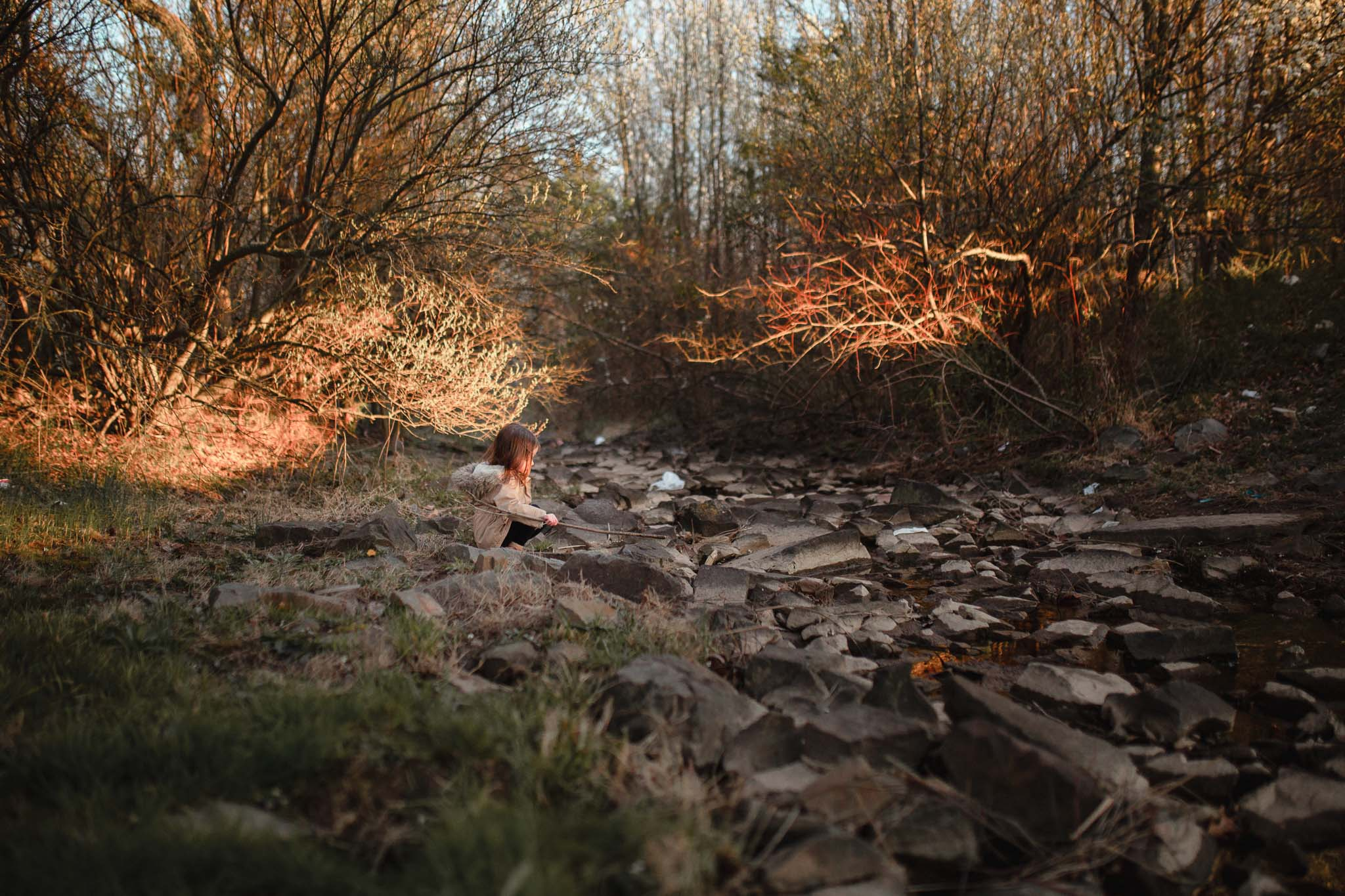 Toddler in a brown coat sits near a creek and uses a stick to move some rocks in Ashburn, Virginia