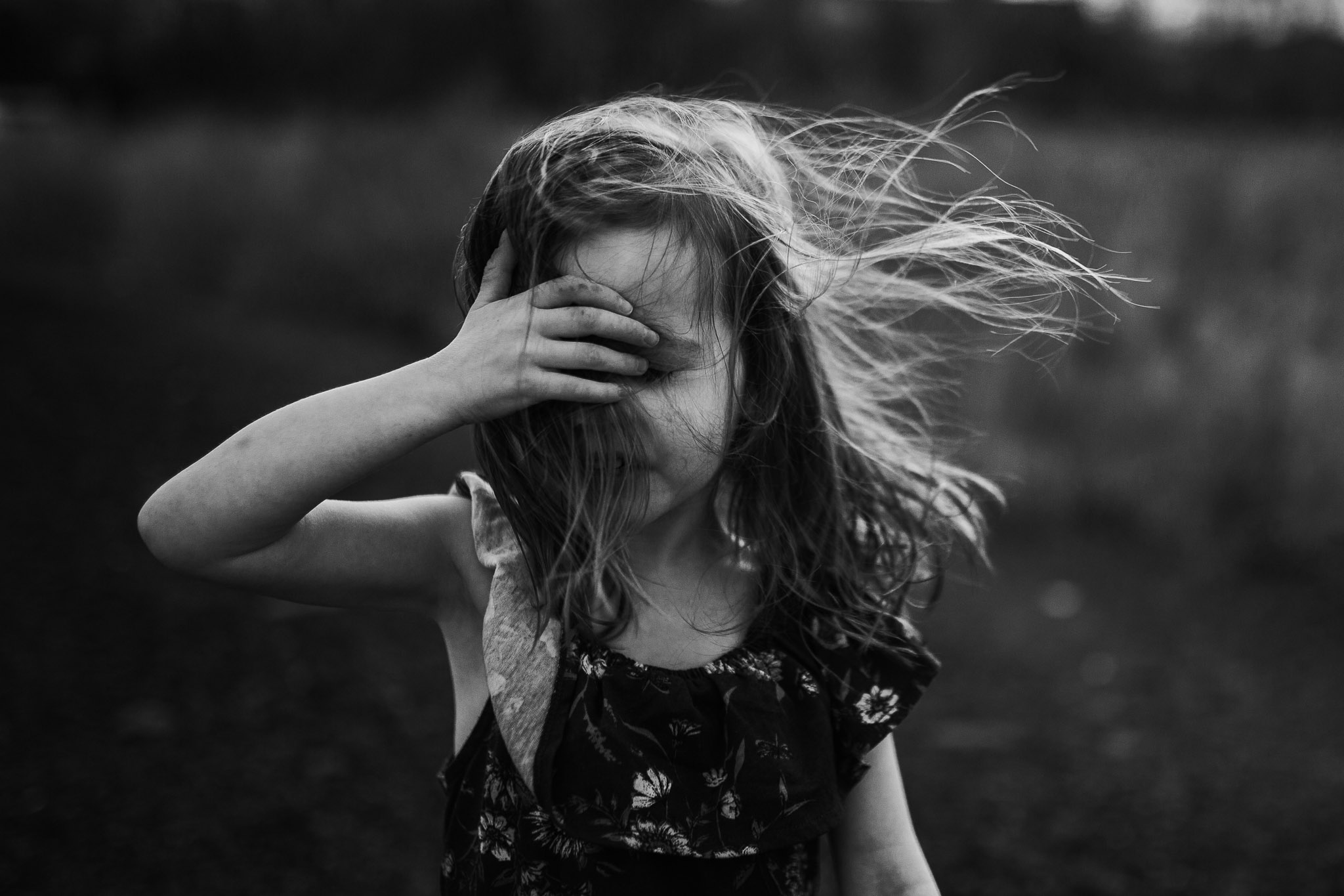 Black and white; girl in a floral dress tries to pull the hair out of her face as the wind blows it in every direction in Ashburn, Virginia